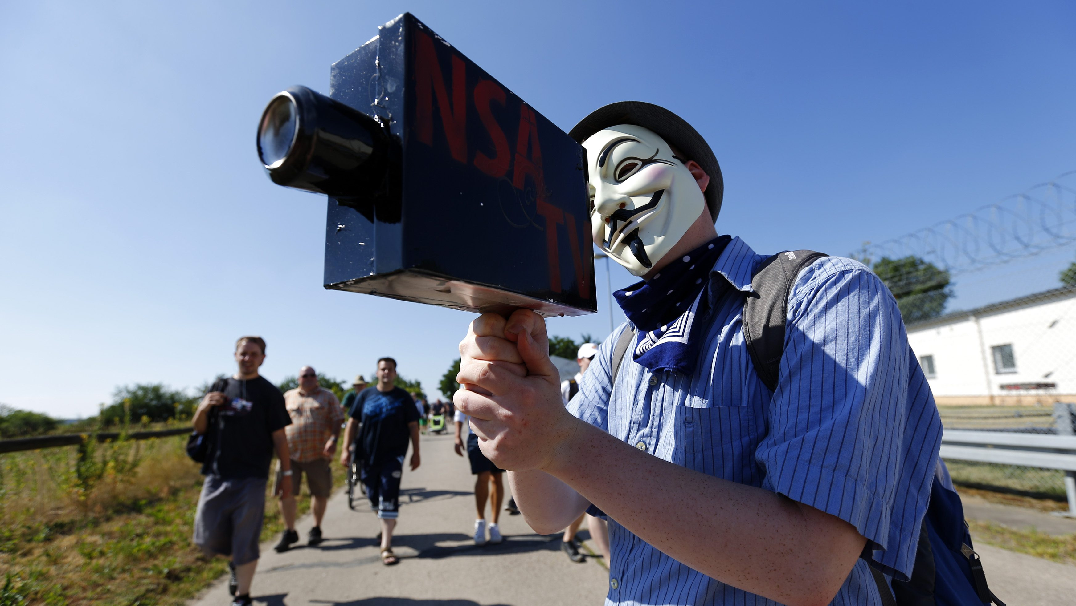 """A protester wearing a Guy Fawkes mask holds a paper-made mock TV camera during a demonstration against the National Security Agency (NSA) and in support of U.S. whistleblower Edward Snowden, outside the """"Dagger Complex"""", which is used by the U.S. Army intelligence services, in Griesheim, 20 km (12.4 miles) south of Frankfurt, July 20, 2013."""
