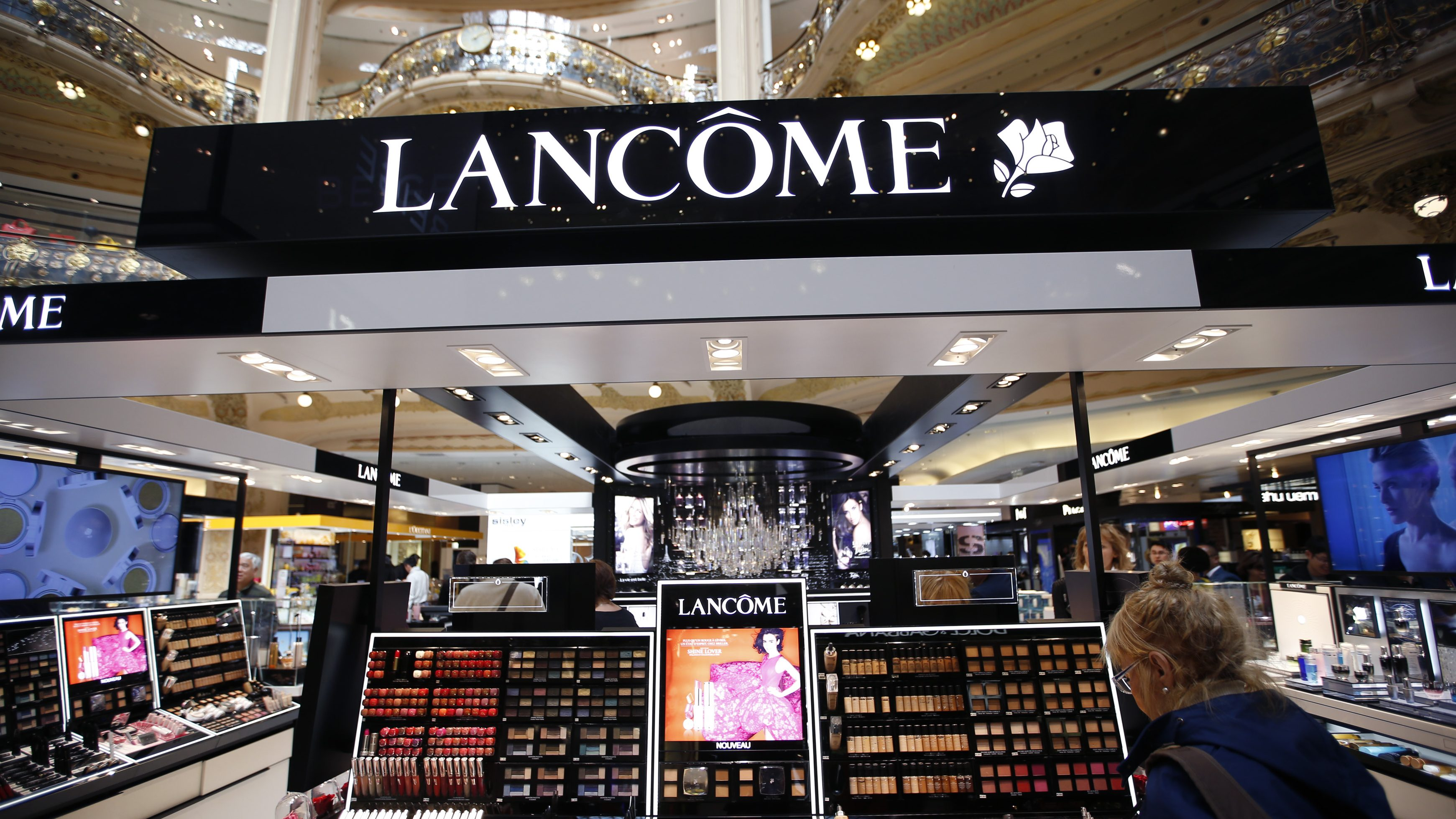 A woman stands in front of a Lancome counter, the cosmetics and perfume brand of French cosmetics group L'Oreal, at a department store in Paris April 20, 2015. L'Oreal posted a 14.1 percent rise in first-quarter sales on Monday, helped by the weak euro and resilient demand for luxury goods products such as Yves Saint Laurent's Black Opium perfume.  REUTERS/Charles Platiau - RTX19JF2