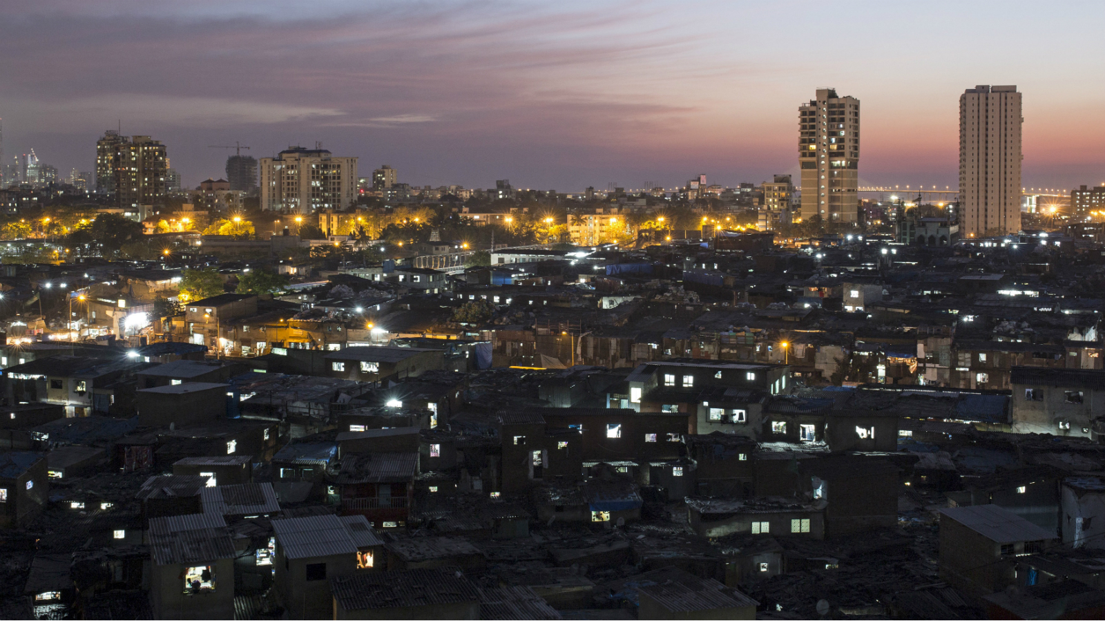 High-rise residential towers are seen behind shanties in Dharavi, one of Asia's largest slums, in Mumbai March 18, 2015. In Mumbai, the windows of new high-rise apartment blocks, old low-rise residential buildings and shantytown shacks portray the disparity in living conditions and incomes in the Indian city. Rents for a place to live range from more than $2,000 to less than $5 a month