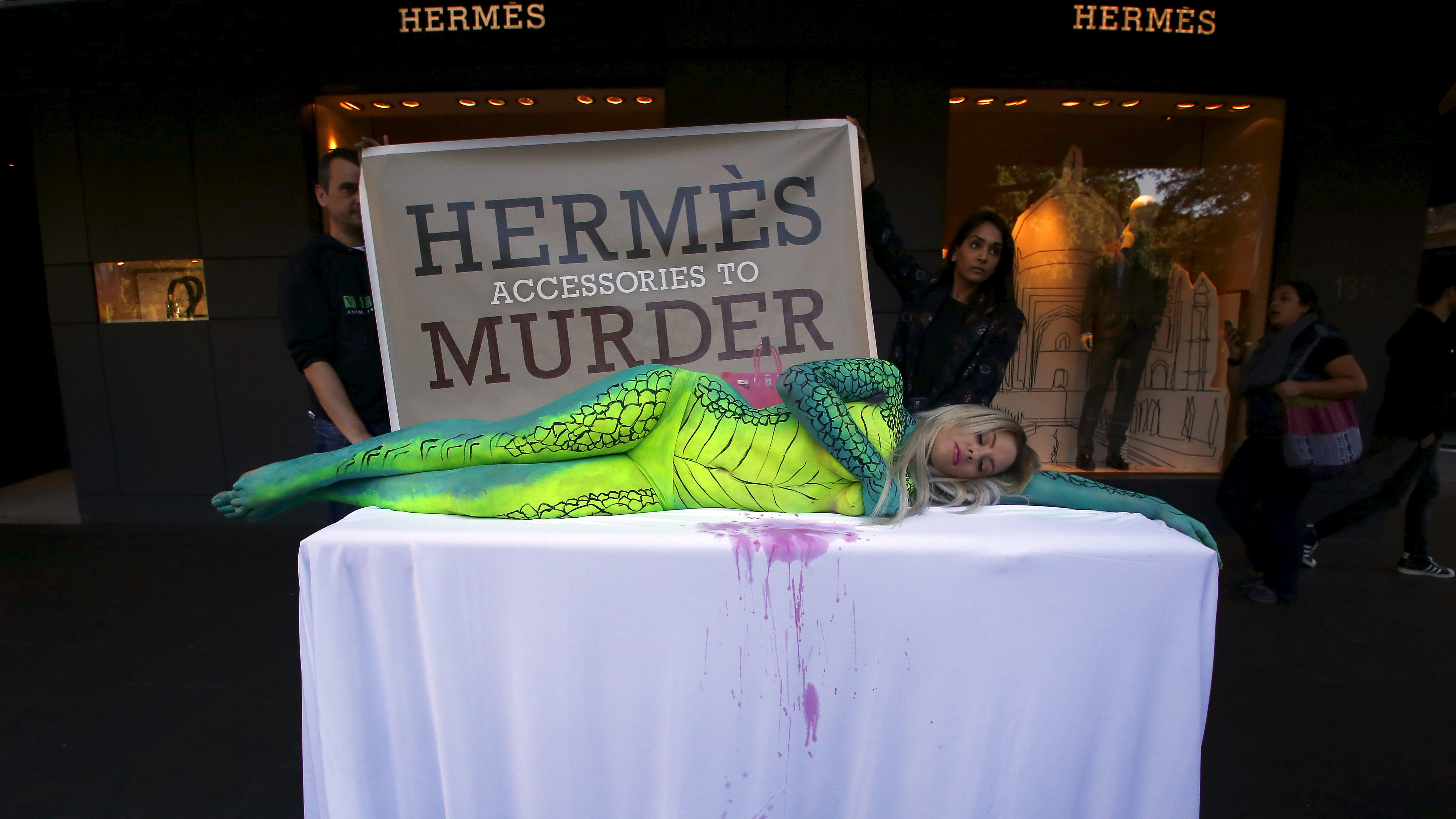 Australian model Rochelle Relf, painted as a crocodile, lies on a table during a protest against the use of crocodile skins, outside luxury product store Hermes in central Sydney, Australia, August 11, 2015. Animal rights organisation People for the Ethical Treatment of Animals (PETA) held the protest claiming that Hermes uses crocodile skins for some of their products from suppliers that harm the reptiles. REUTERS/David Gray