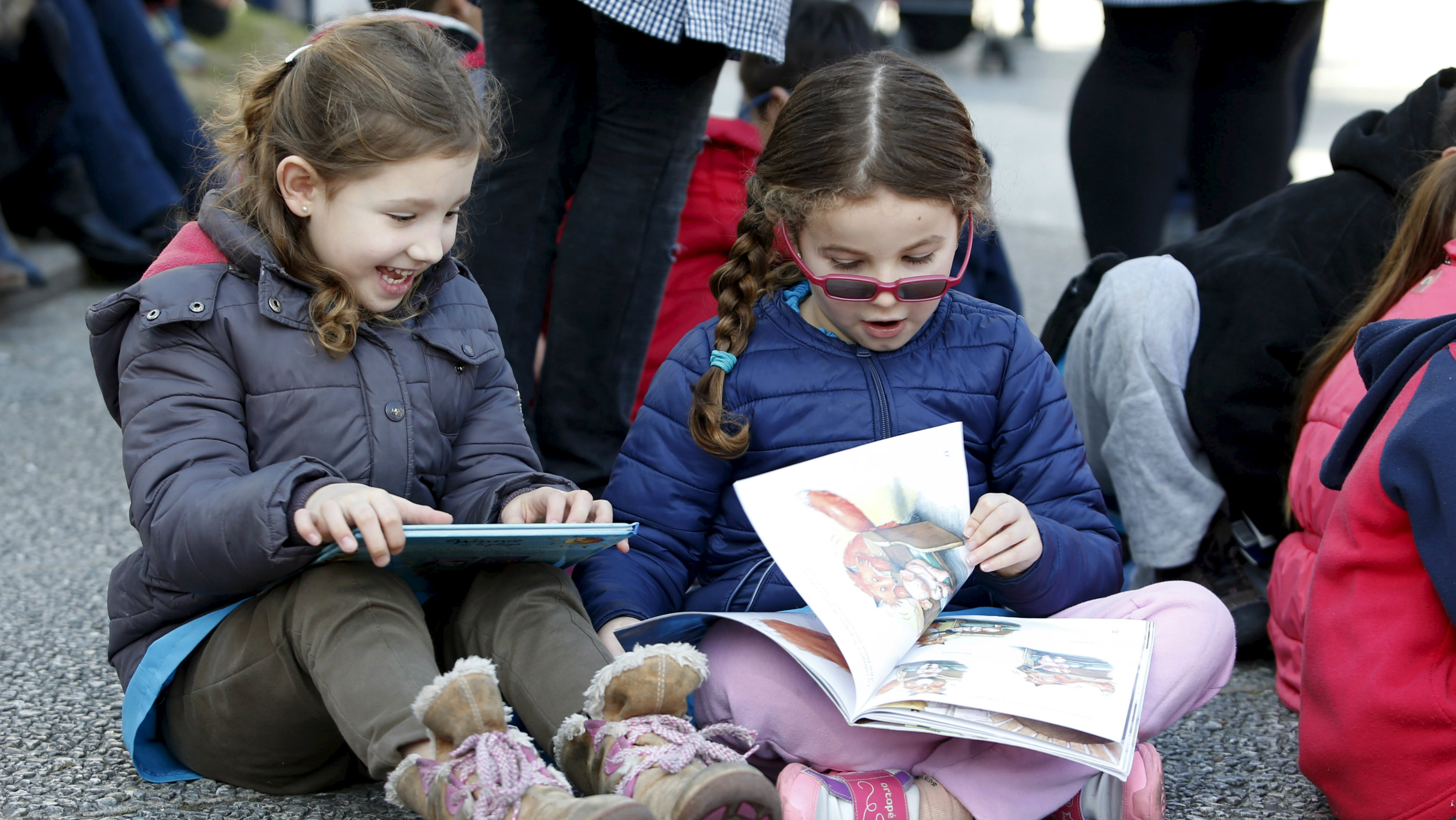 """Children read books at Montevideo's Independencia square while participating in the activity """"Al Aire..."""