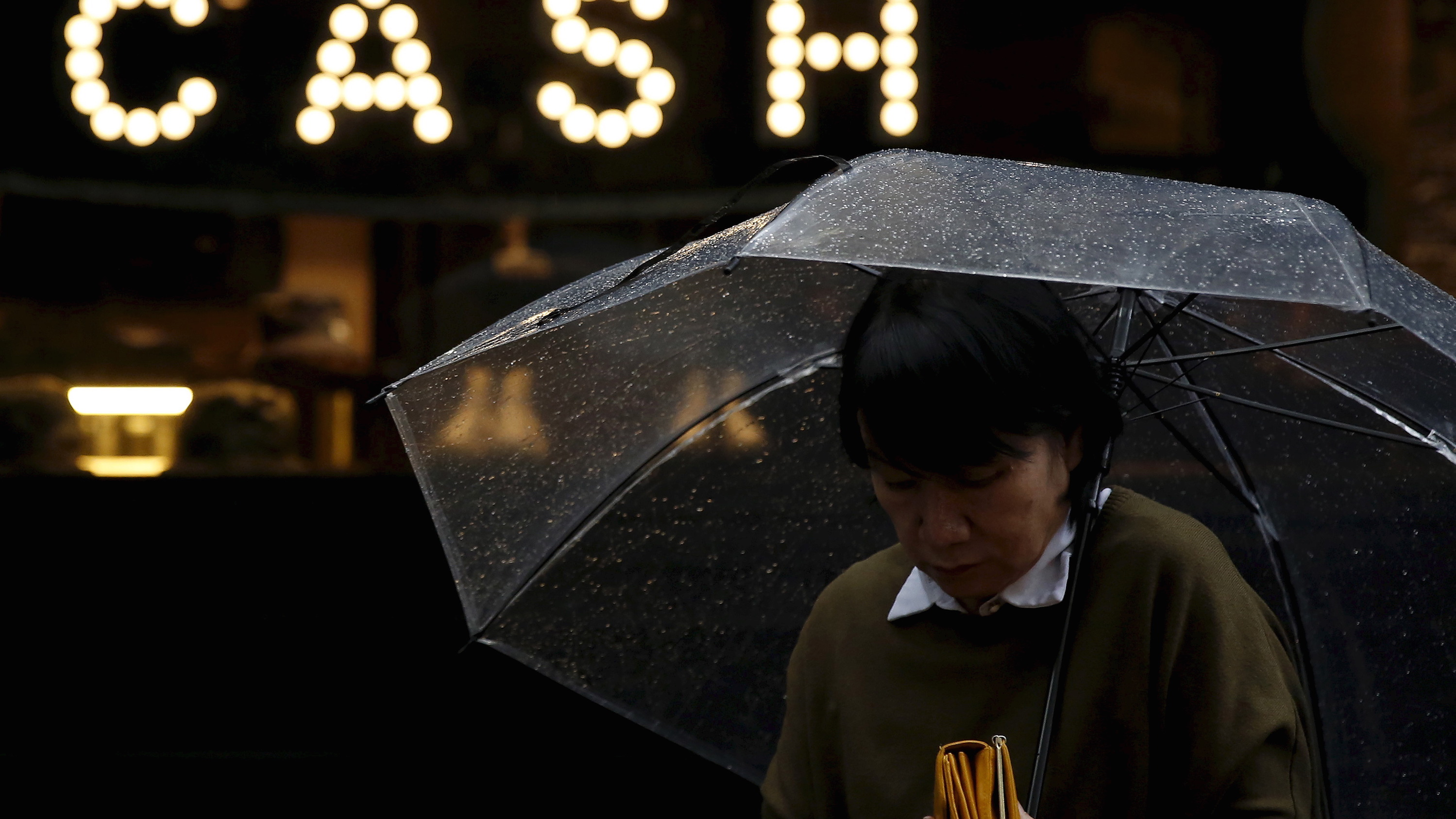 """A pedestrian holding an umbrella and her wallet walks past the word """"CASH"""" part of a sign on a street at a shopping district in Tokyo"""