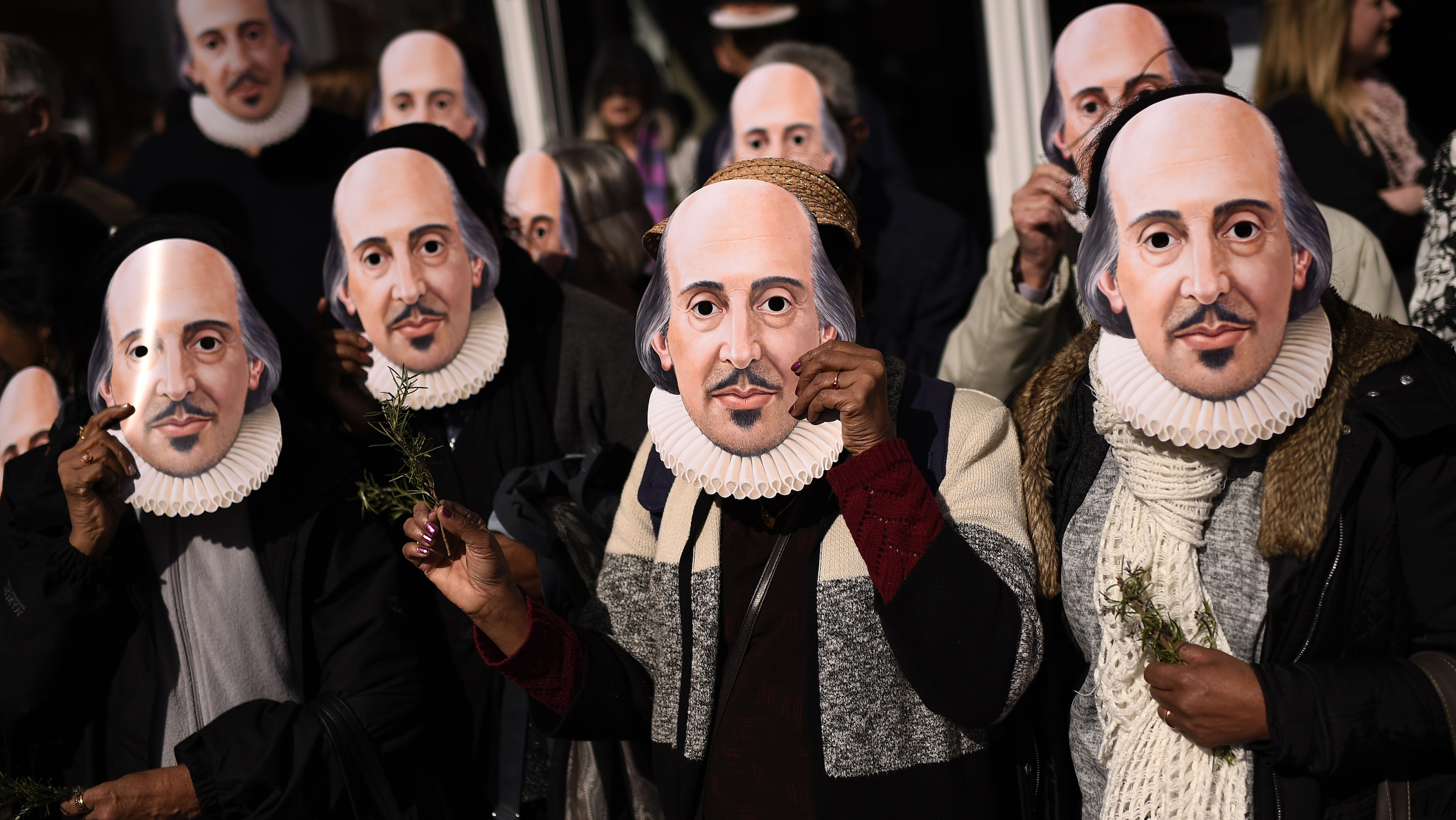 People hold up face masks with William Shakespeare's portrait during celebrations to mark the 400th anniversary of the playwright's death in the city of his birth, Stratford-Upon-Avon, Britain, April 23, 2016. REUTERS/Dylan Martinez - RTX2BAP8
