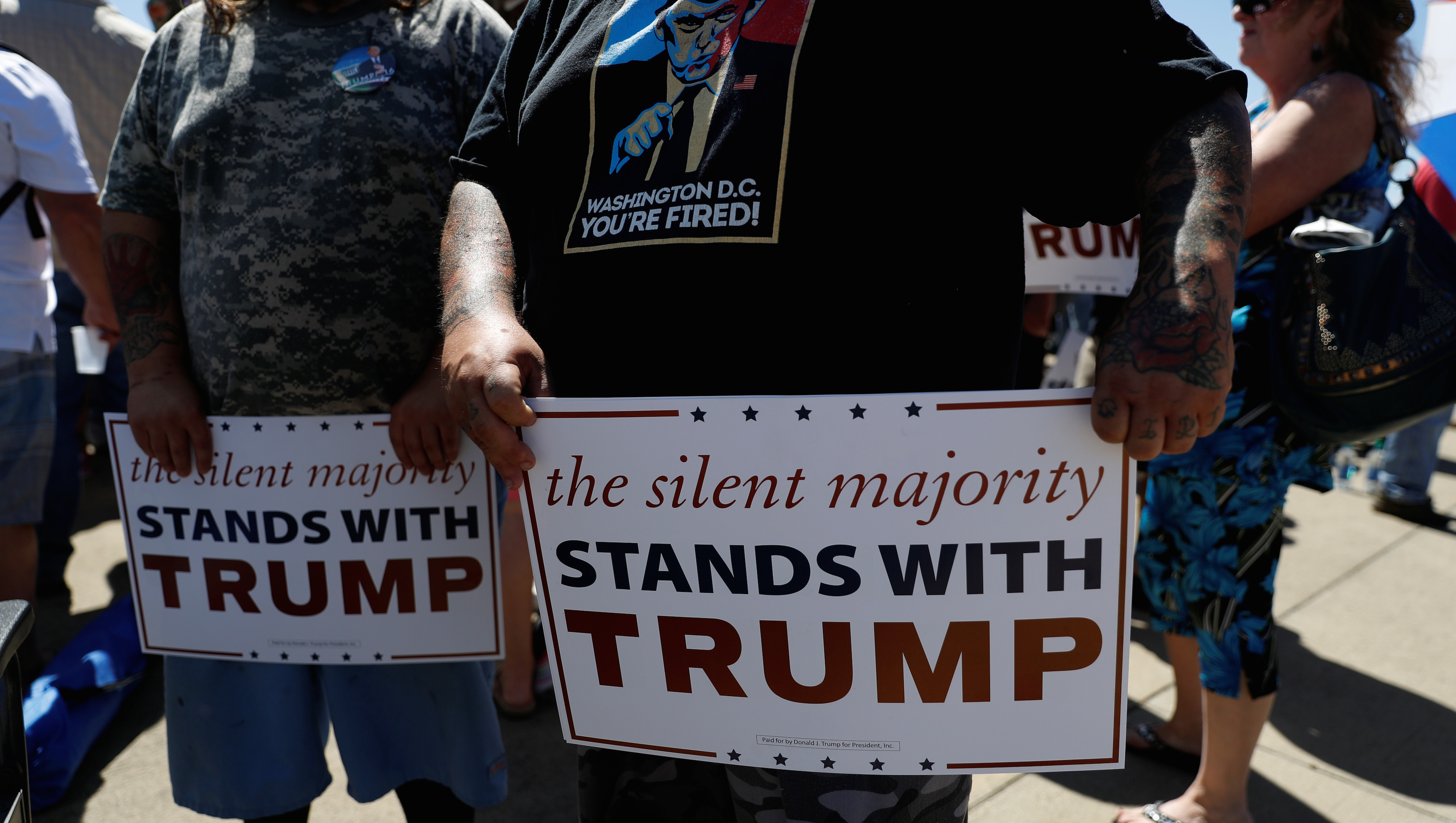 Supporters of Republican U.S. presidential candidate Trump hold signs while waiting for a campaign rally in Redding, California