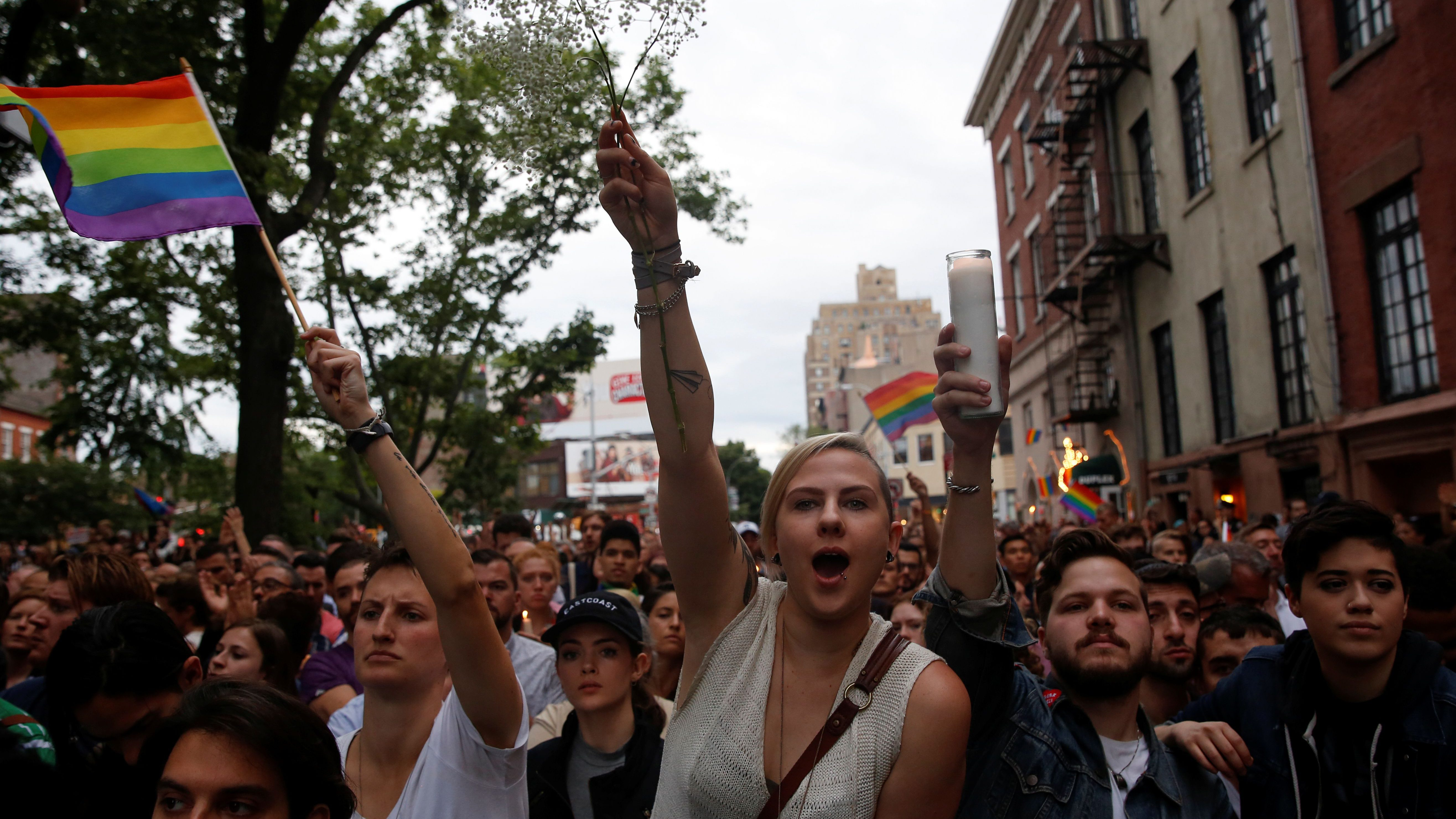 People cheer during a vigil outside The Stonewall Inn remembering the victims of the Orlando massacre in New York, U.S., June 13, 2016.  - RTX2G2J0