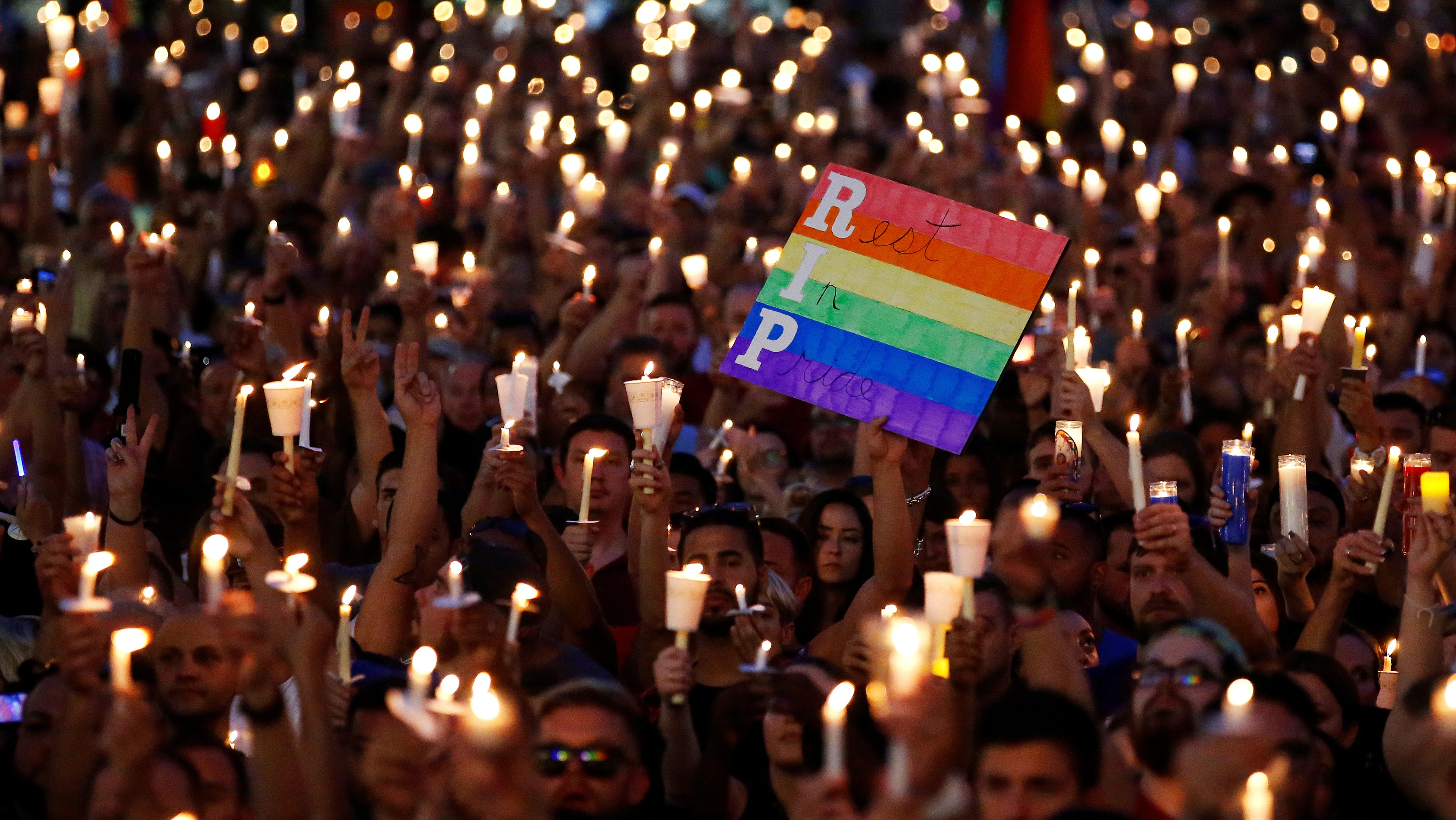 People take part in a candlelight memorial service the day after a mass shooting at the Pulse gay nightclub in Orlando, Florida, U.S. June 13, 2016. REUTERS/Carlo Allegri     TPX IMAGES OF THE DAY      - RTX2G2MK