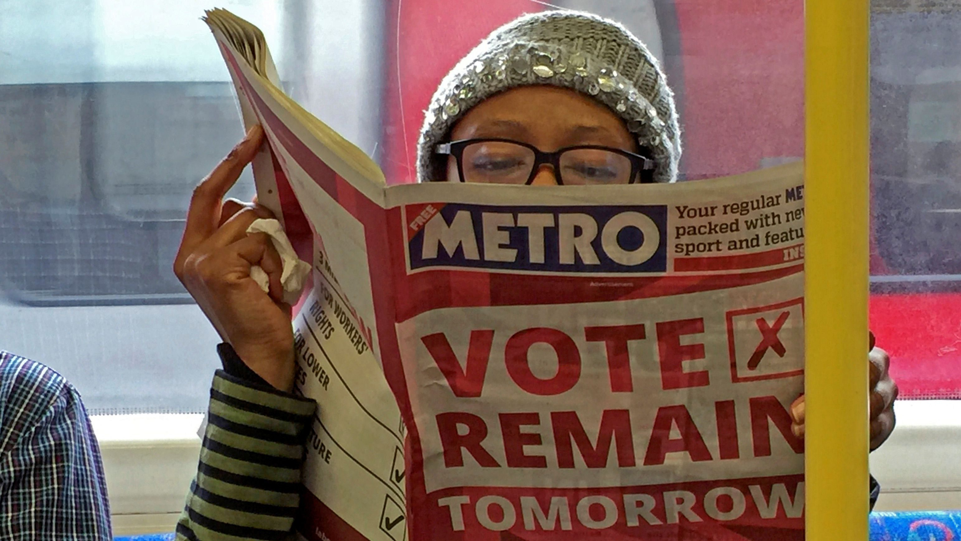 A woman reads a newspaper on the underground in London with a 'vote remain' advert for the BREXIT referendum, Britain June 22, 2016. REUTERS/Russell Boyce  - RTX2HIDZ