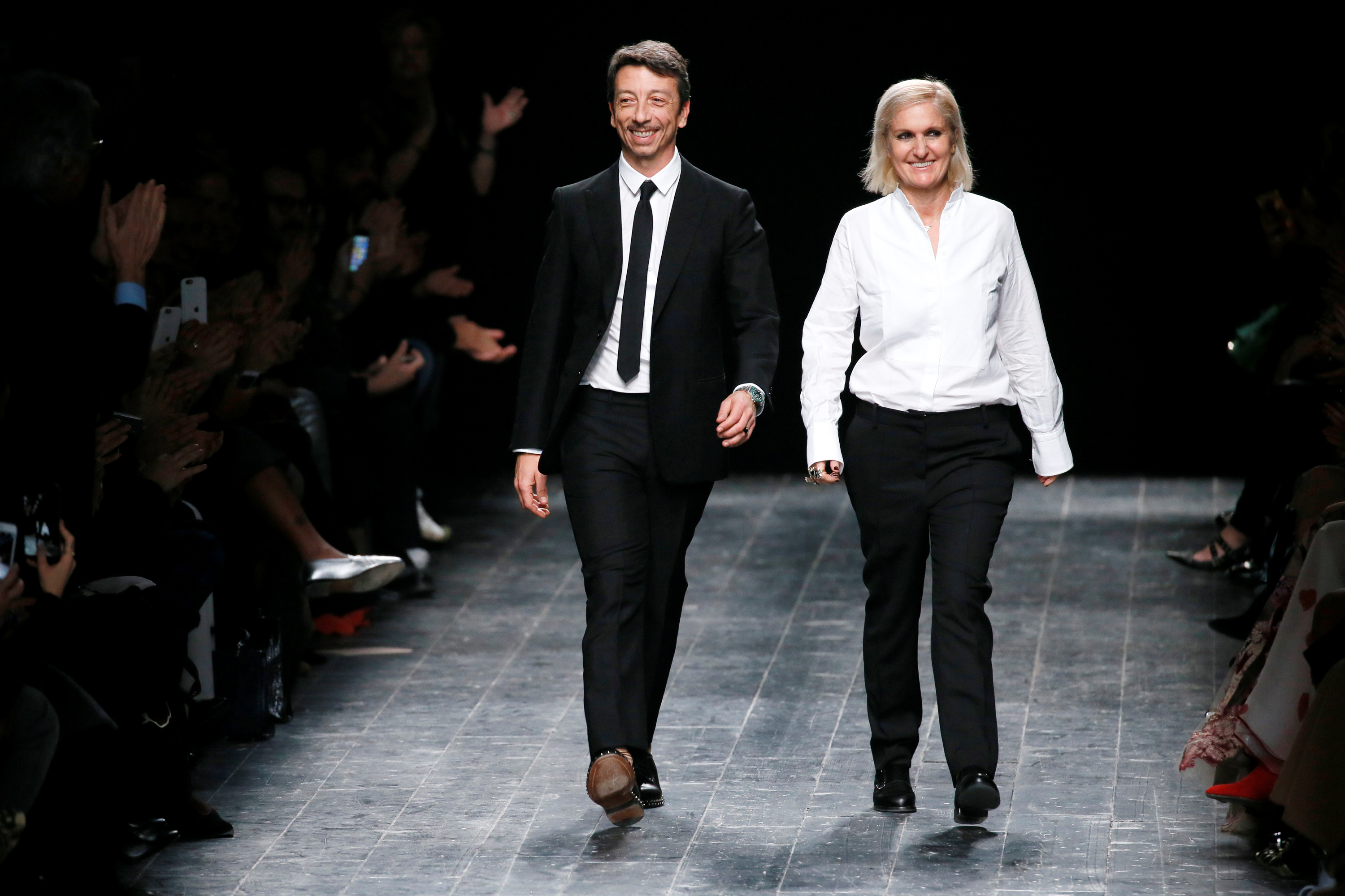 Italian designers Maria Grazia Chiuri and Pier Paolo Piccioli appear at the end of their Fall/Winter 2016/2017 women's ready-to-wear collection for fashion house Valentino in Paris, France, March 8, 2016. REUTERS/Gonzalo Fuentes/File Photo - RTX2HSU2