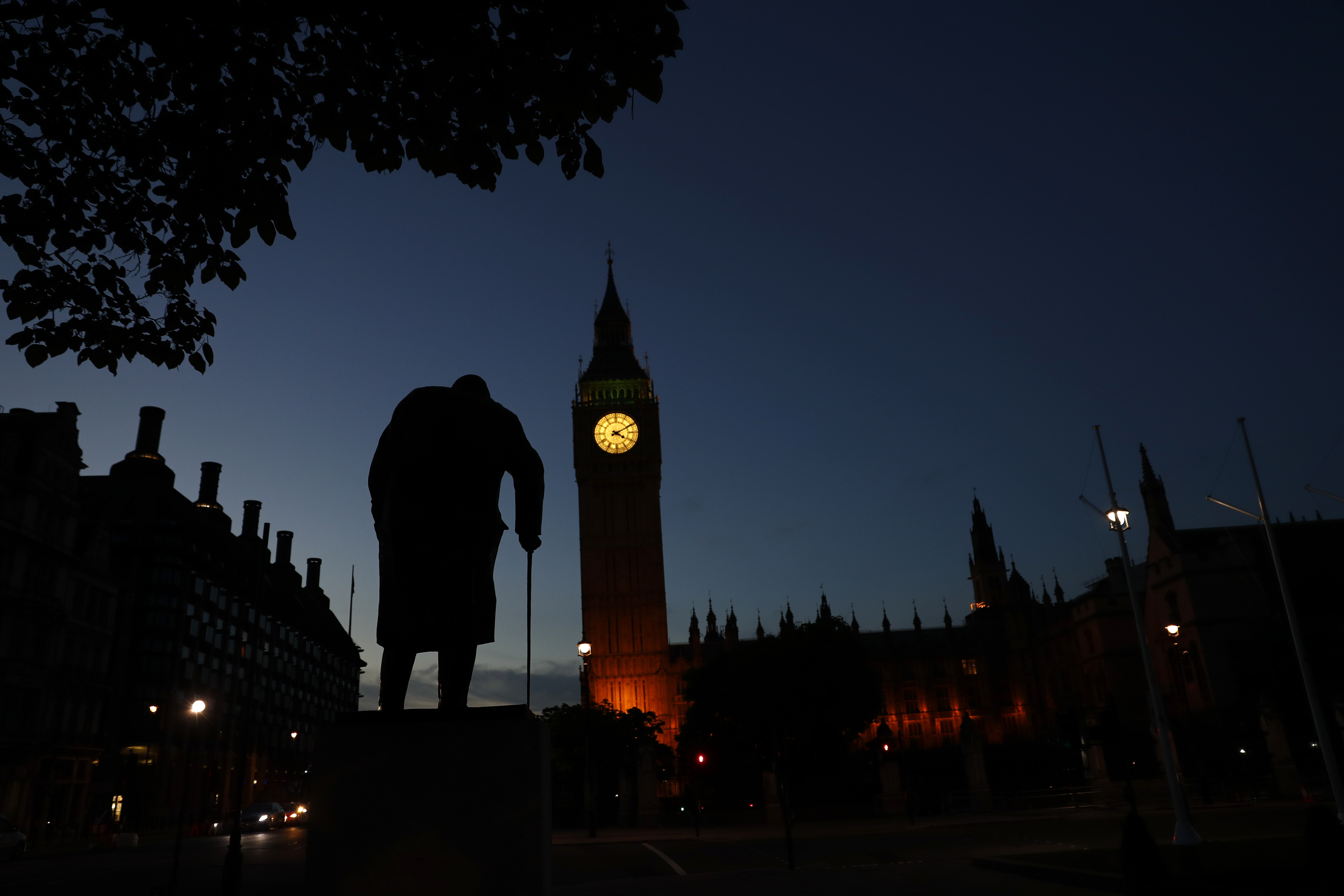 Dawn breaks behind the Houses of Parliament and the statue of Winston Churchill in Westminster, London, Britain