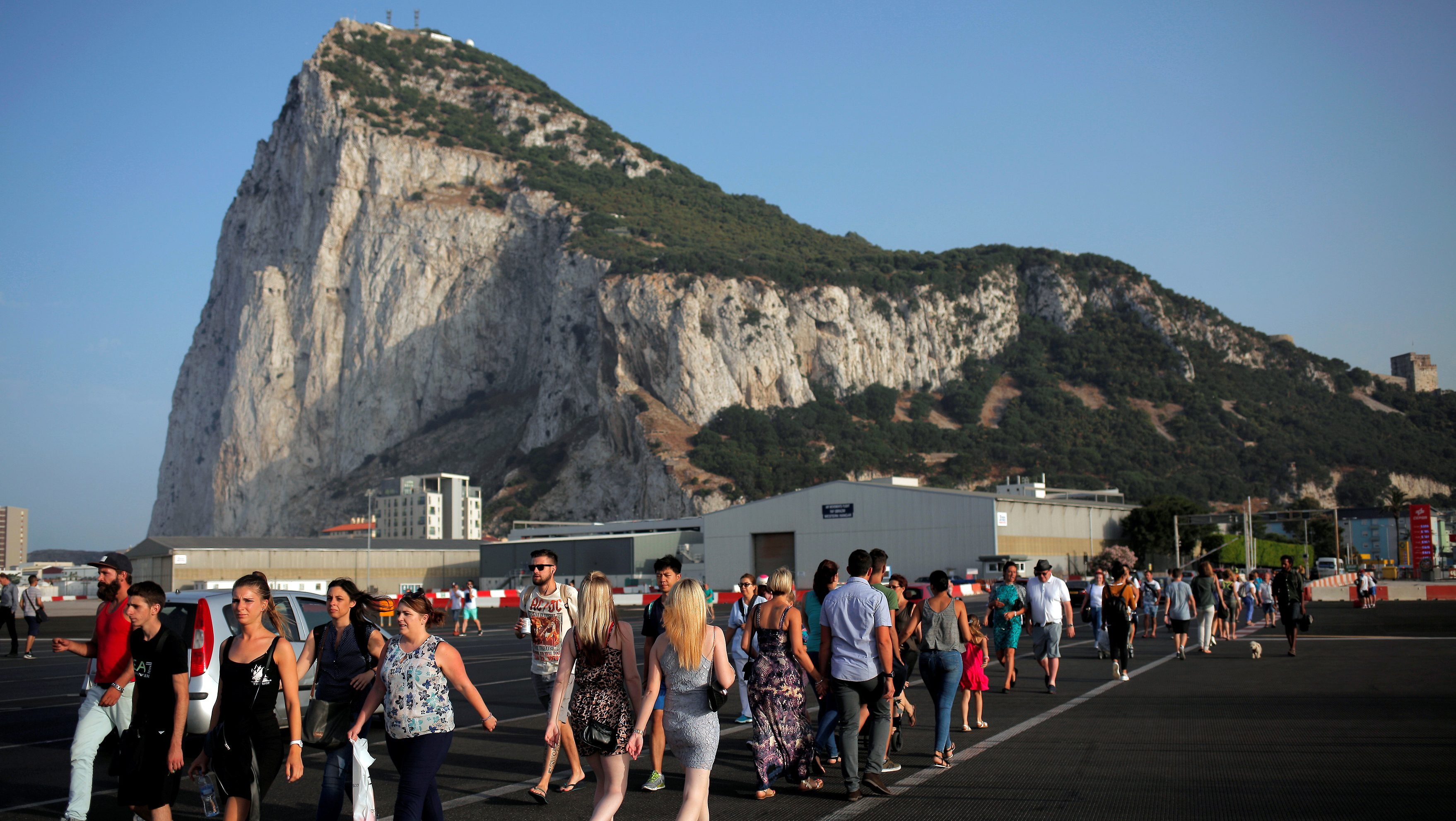 Pedestrians cross the tarmac at Gibraltar International Airport in front of the Rock near the border with Spain in the British overseas territory of Gibraltar, historically claimed by Spain, June 24, 2016, after Britain voted to leave the European Union in the EU BREXIT referendum. REUTERS/Jon Nazca - RTX2I2LA