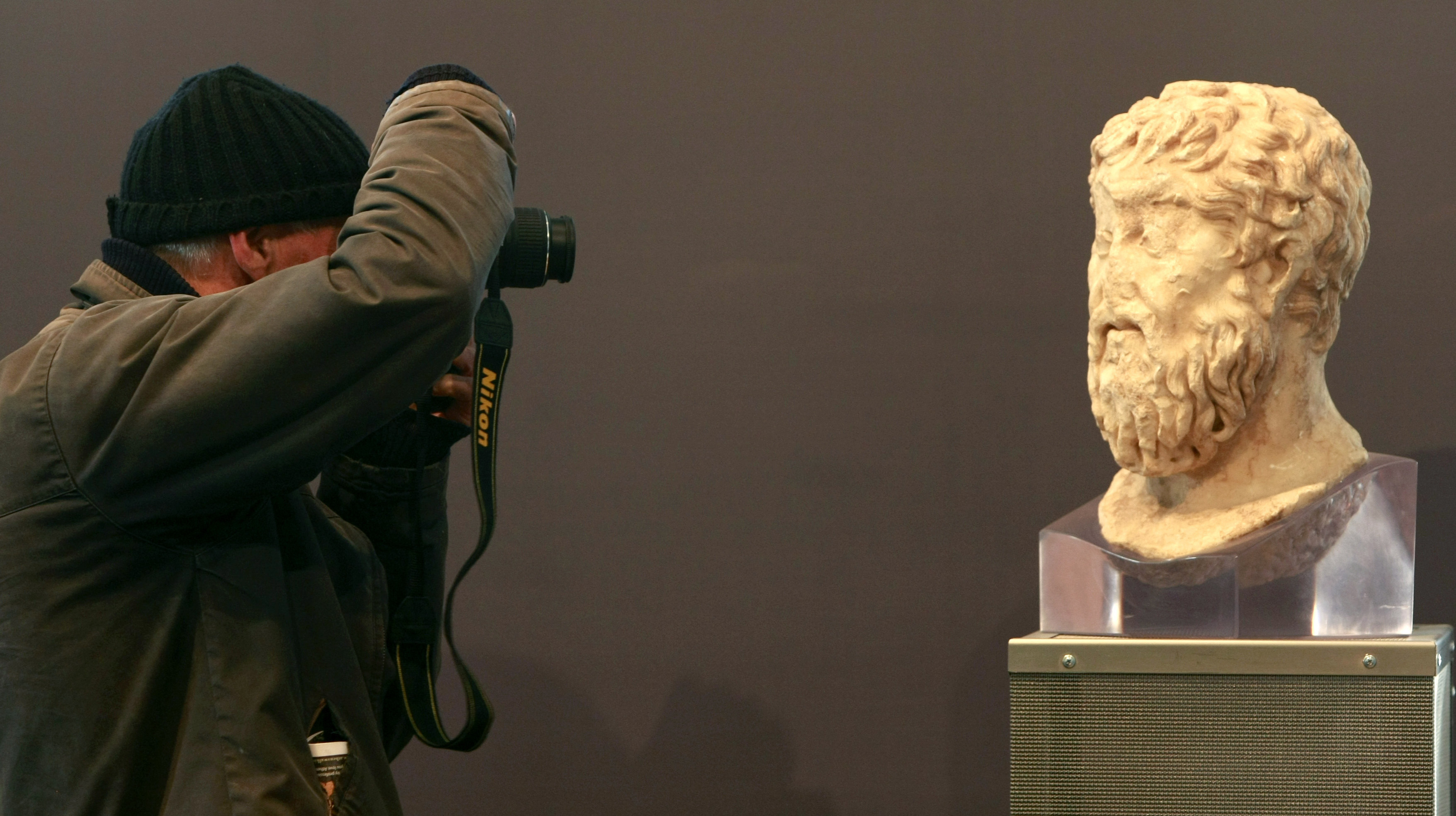 A man photographs a Plato statue inside the new Acropolis museum in Athens