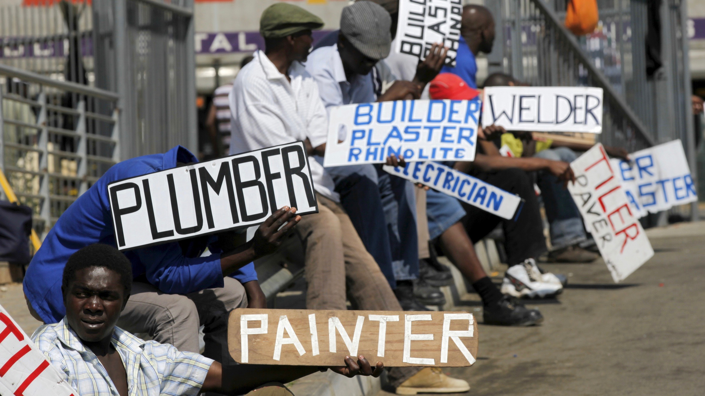 Men hold placards offering temporal employment services in Glenvista, south of Johannesburg, October 7, 2010.
