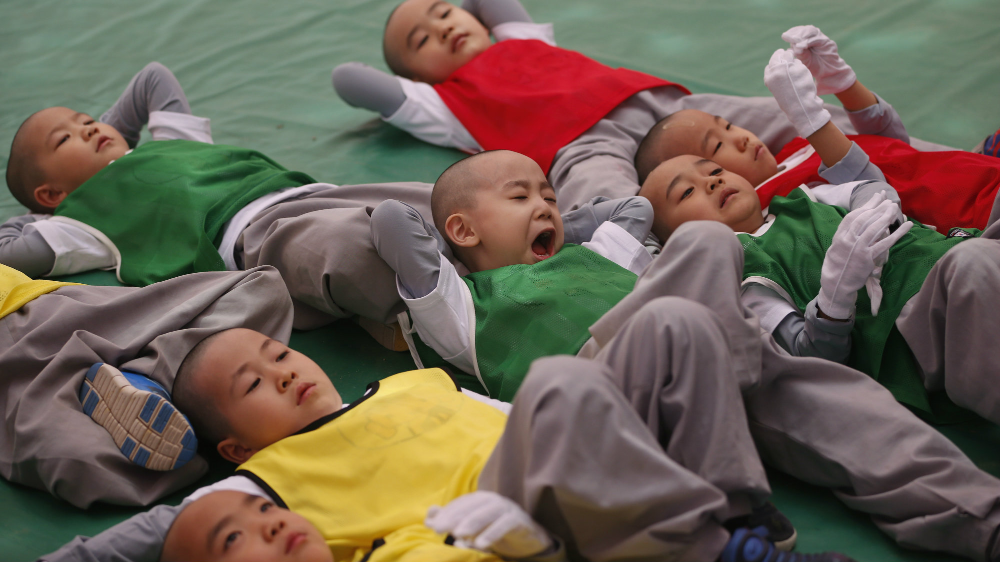 A boy yawns as he and others, who are experiencing the lives of Buddhist priests by staying in a temple for two weeks as novice monks, rest before a friendly soccer match to celebrate the upcoming birthday of Buddha at Jogye temple in Seoul, May 14, 2013.