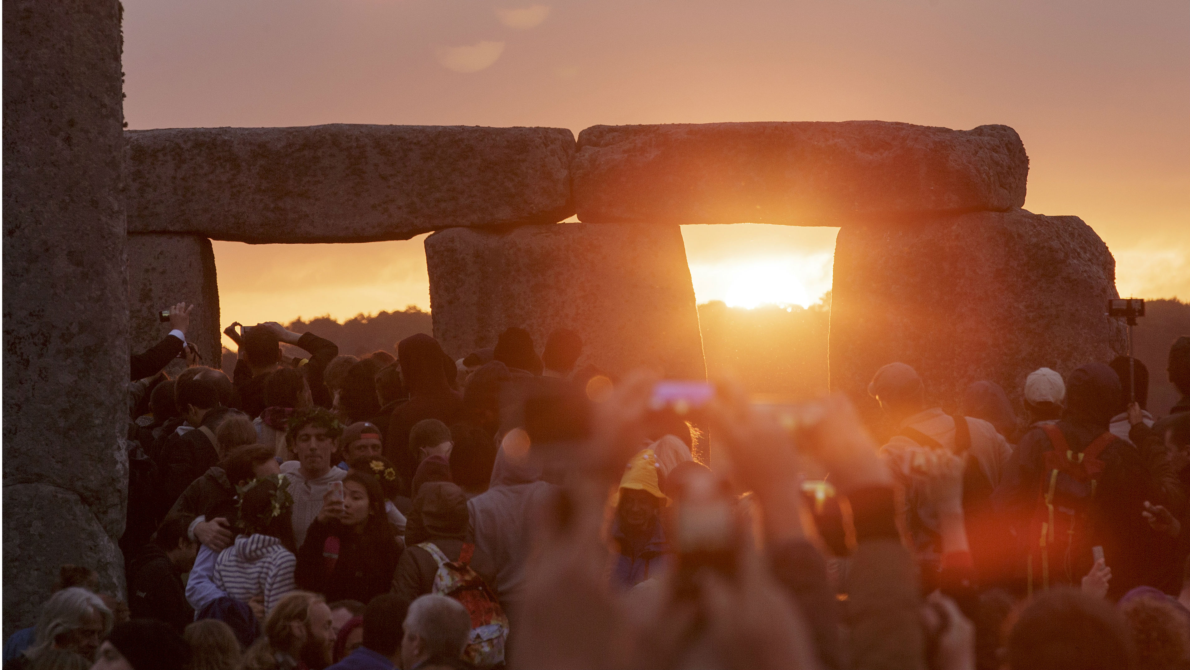The sun rises as thousands of revellers gathered at the ancient stone circle Stonehenge to celebrate the Summer Solstice, the longest day of the year, near Salisbury, England, Sunday, June 21, 2015.