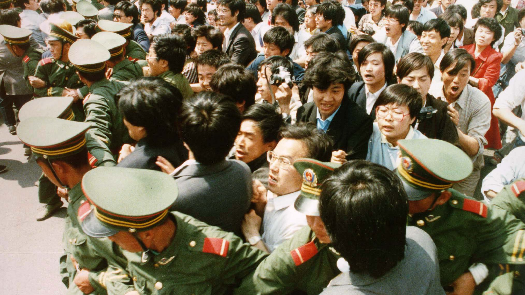 Crowds of jubilant students surge through a police cordon before pouring into Tiananmen Square on June 4, 1989 during a pro-democracy demonstration. This year marks the 10th anniversary of the bloody June 4 1989 army crackdown on the pro-democracy movement at Beijing's Tiananmen Square.