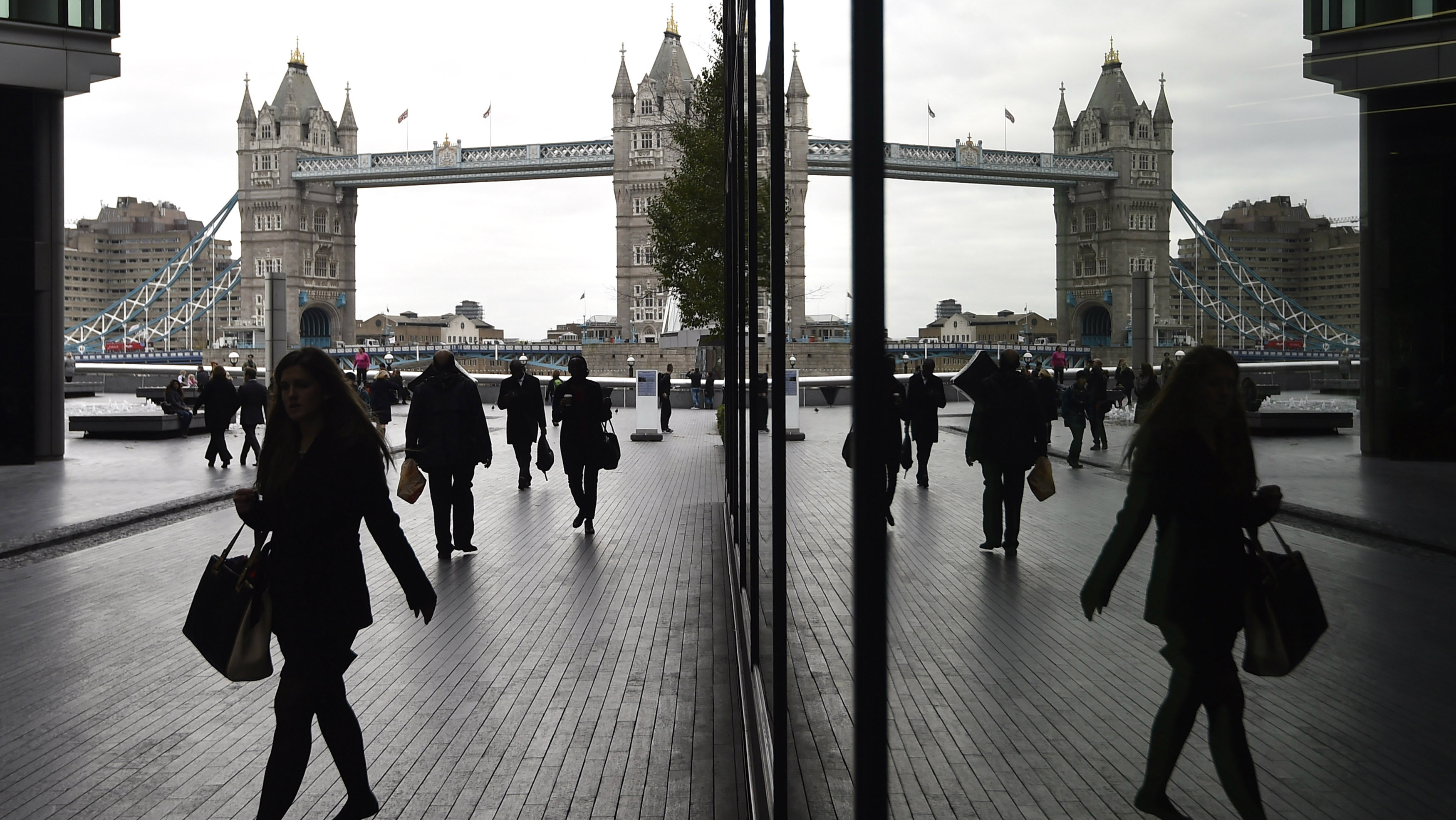 Workers walk through the More London business district with Tower Bridge seen behind in London, November 11, 2015. REUTERS/Toby Melville