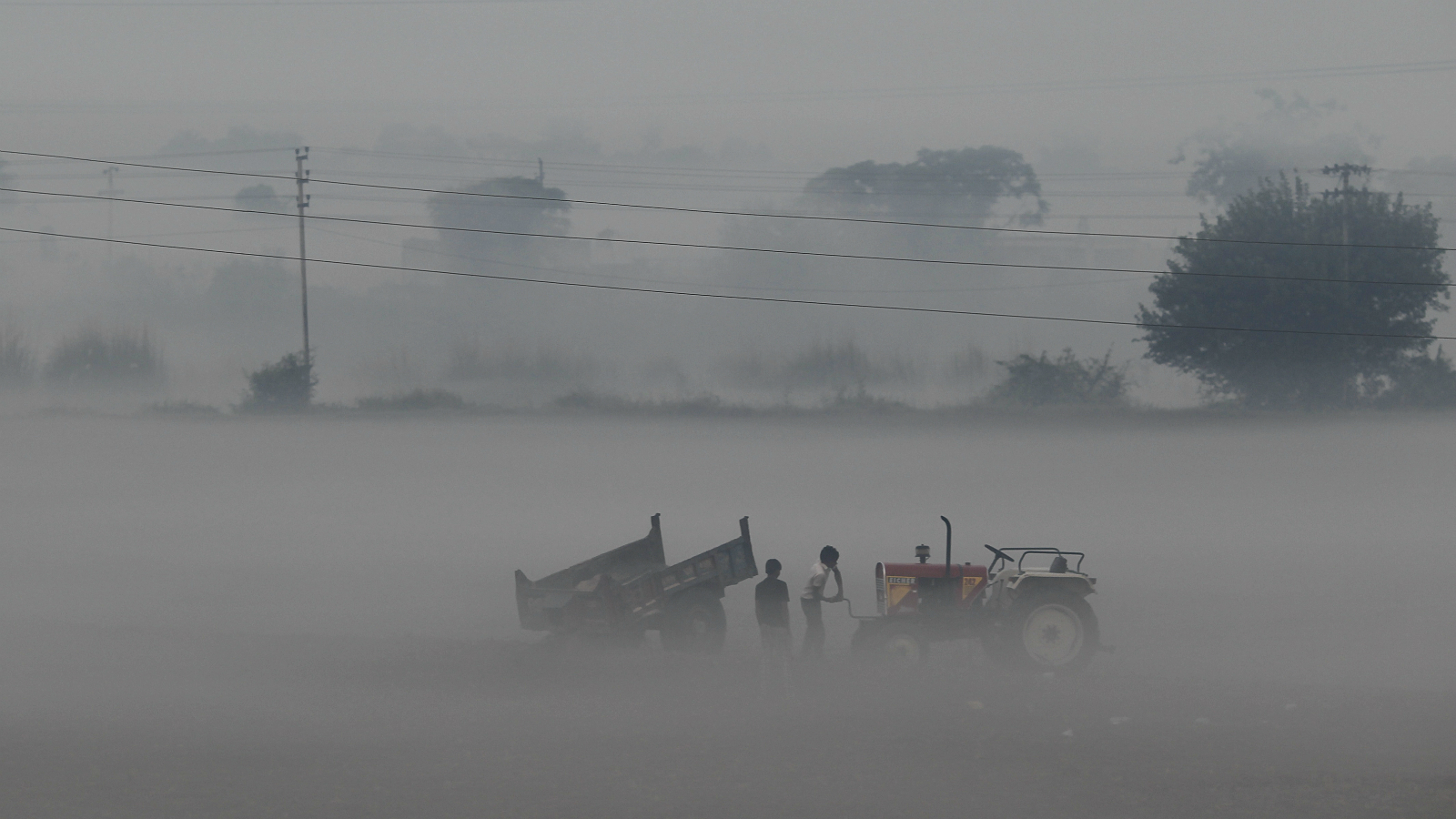 A man starts the engine of a tractor during a foggy morning in a field along the Delhi-Noida highway October 26, 2012.