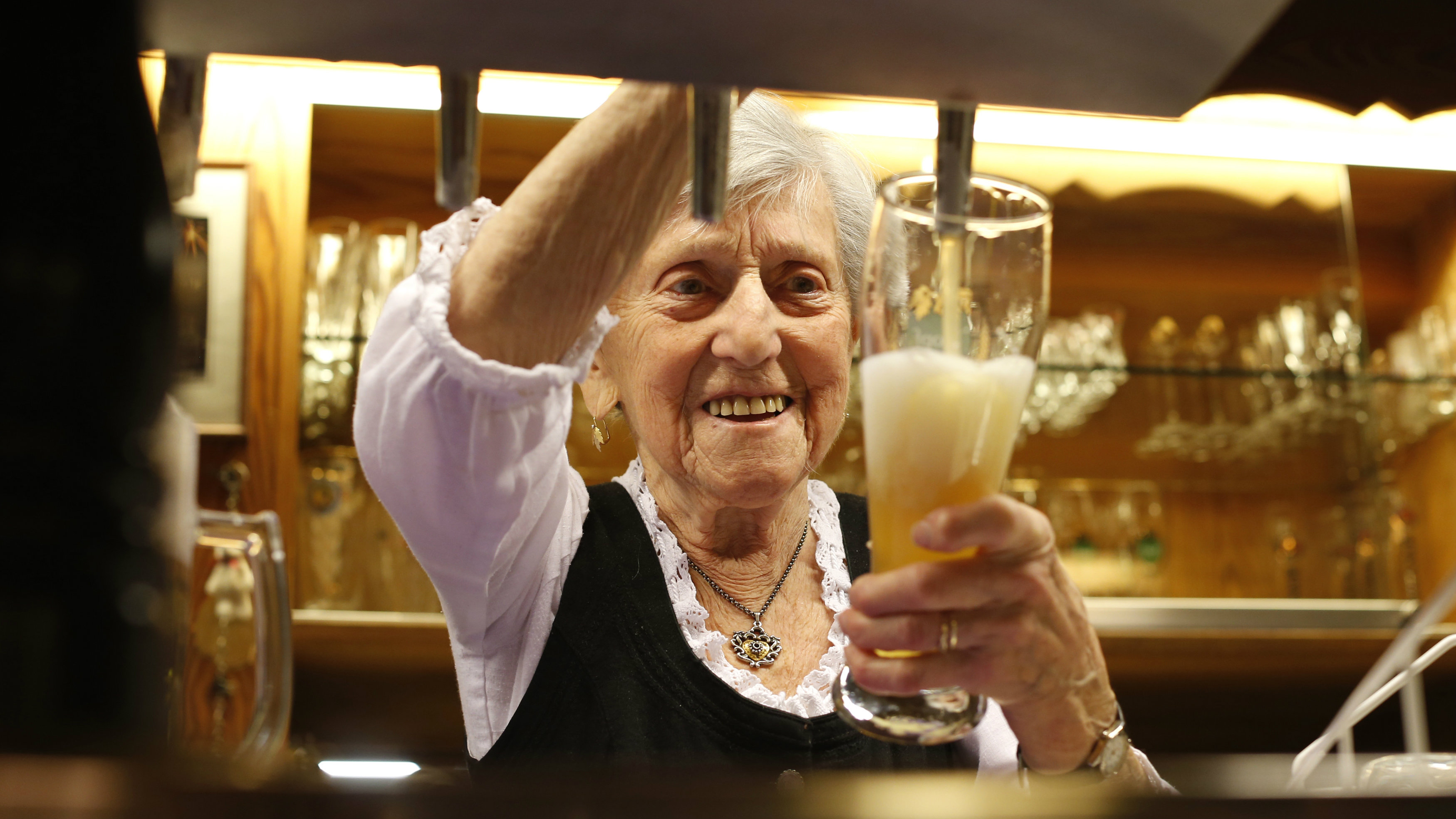 German waitress Kathi Kink, aged 91, pours beer into a glass in the 'Zum Goldenen Tal' restaurant in Naring near Weyarn, southern Germany February 1, 2015. Since 1939 at the age of 16, Kathi has worked as a waitress at the 'Zum Goldenen Tal' restaurant in Naring, serving her guests drinks and meals between five and 11 hours per day, five days a week. When not working, in her private time Kathi likes to travel the world or reads books. Since 1977 she has worn a mileometer to record her steps and has so far completed a distance of 81,000 kilometres up until the present day. Picture taken February 1. REUTERS/Michaela Rehle (GERMANY - Tags: BUSINESS EMPLOYMENT SOCIETY)