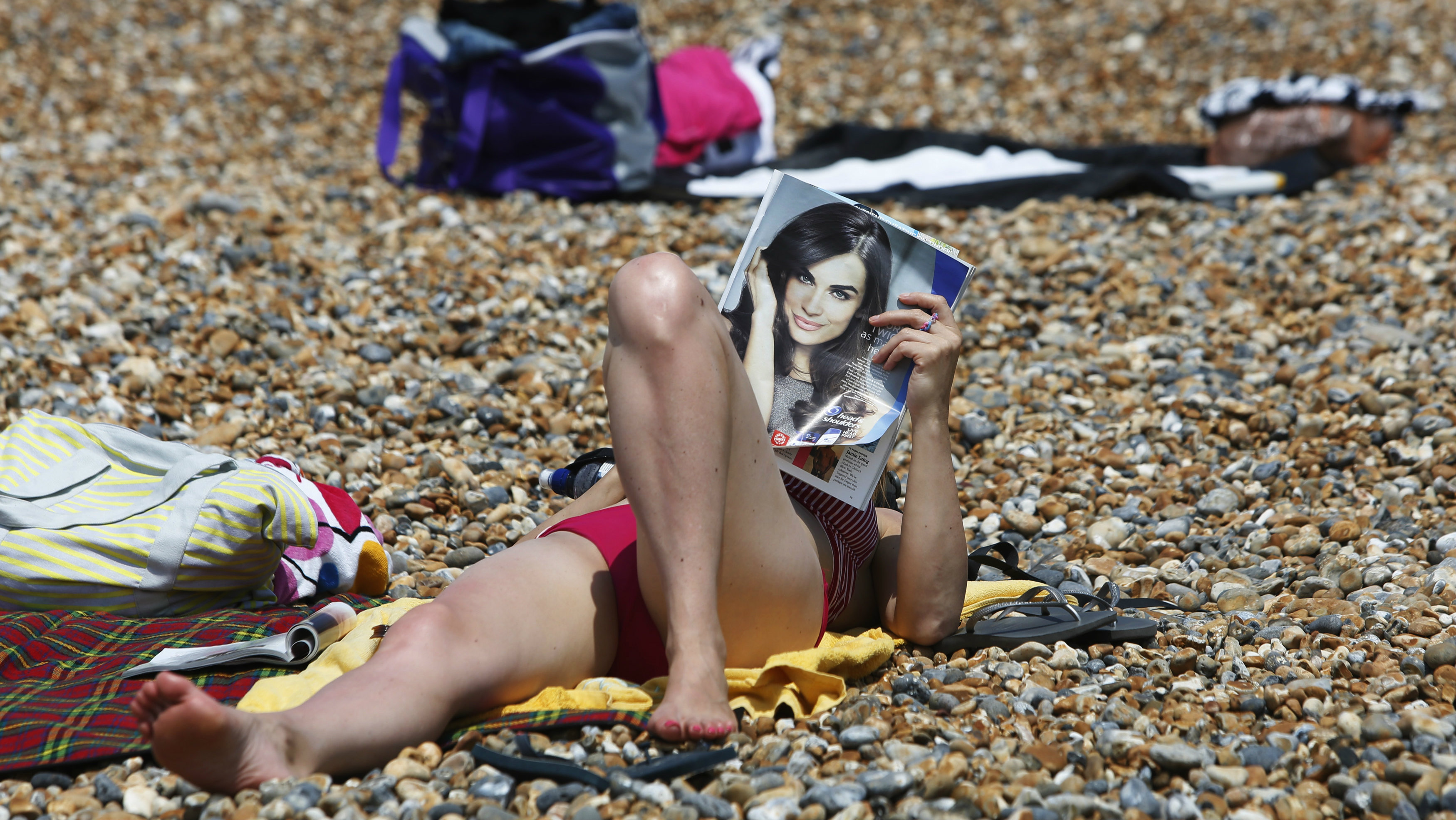 A woman reads a magazine as she sunbathes during the hot summer weather on Brighton beach in southern England July 23, 2014. REUTERS/Luke MacGregor (BRITAIN - Tags: ENVIRONMENT SOCIETY)
