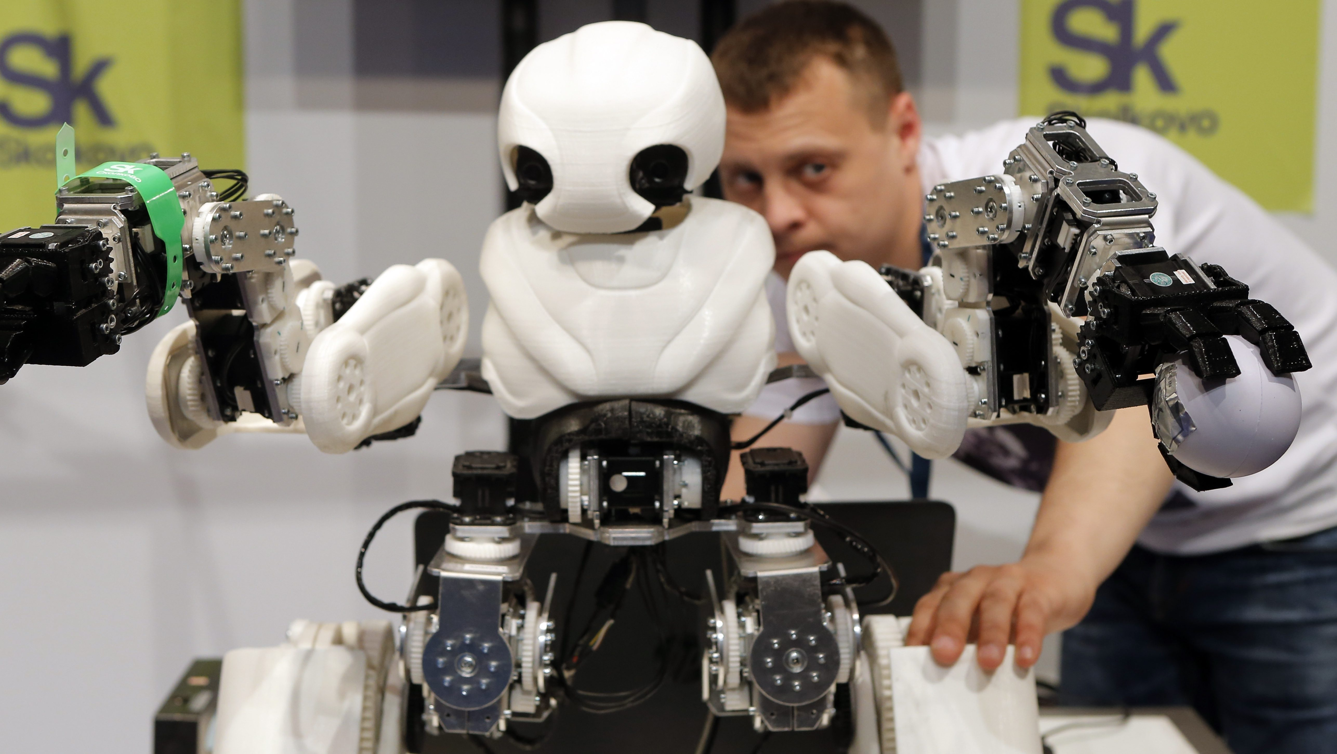 Robot exhibitor Alexander Ganyushkin from Russia presents a prototype robot named Adam during the Innorobo European summit, an event dedicated to the service robotics industry in Aubervilliers, outskirts of Paris, Wednesday, May 25, 2016. (AP Photo/Francois Mori)