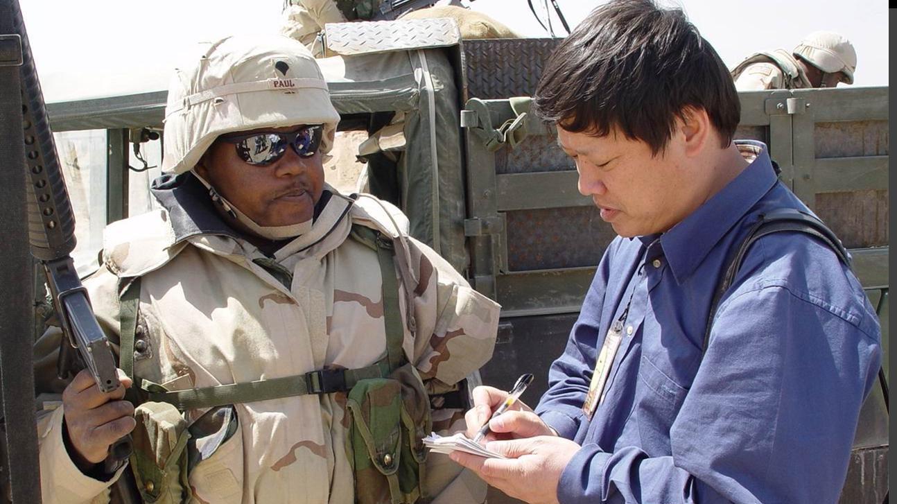 2003年伊拉克战争前夕,胡锡进在科伊边境采访美军士兵。