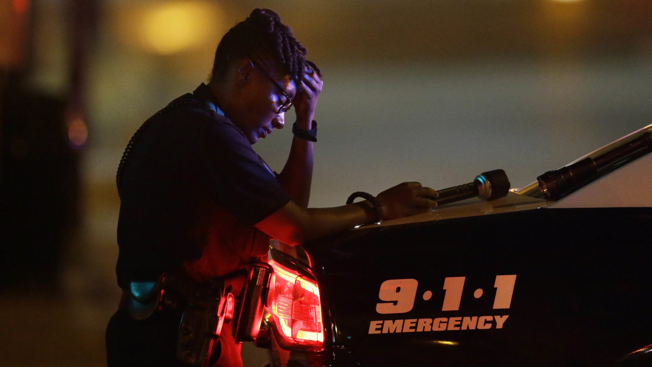 A Dallas police officer, who did not which to be identified, takes a moment as she guards an intersection in the early morning after a shooting in downtown Dallas, Friday, July 8, 2016. At least two snipers opened fire on police officers during protests in Dallas on Thursday night; some of the officers were killed, police said. (AP Photo/LM Otero)