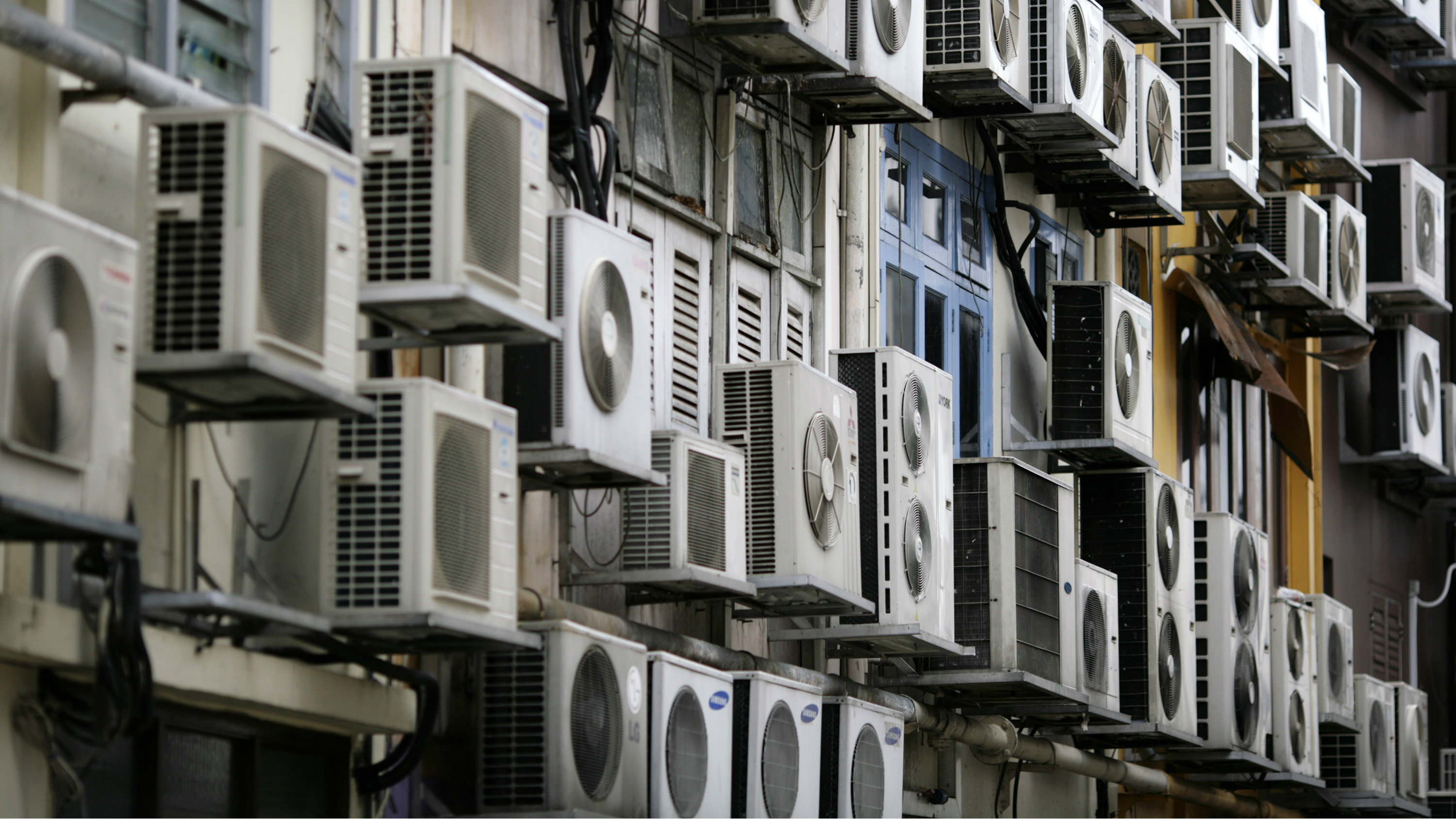 Rows of air conditioners are seen on the walls of a building in Singapore's financial district December 11, 2009. REUTERS/Vivek Prakash (SINGAPORE ENVIRONMENT ENERGY POLITICS)