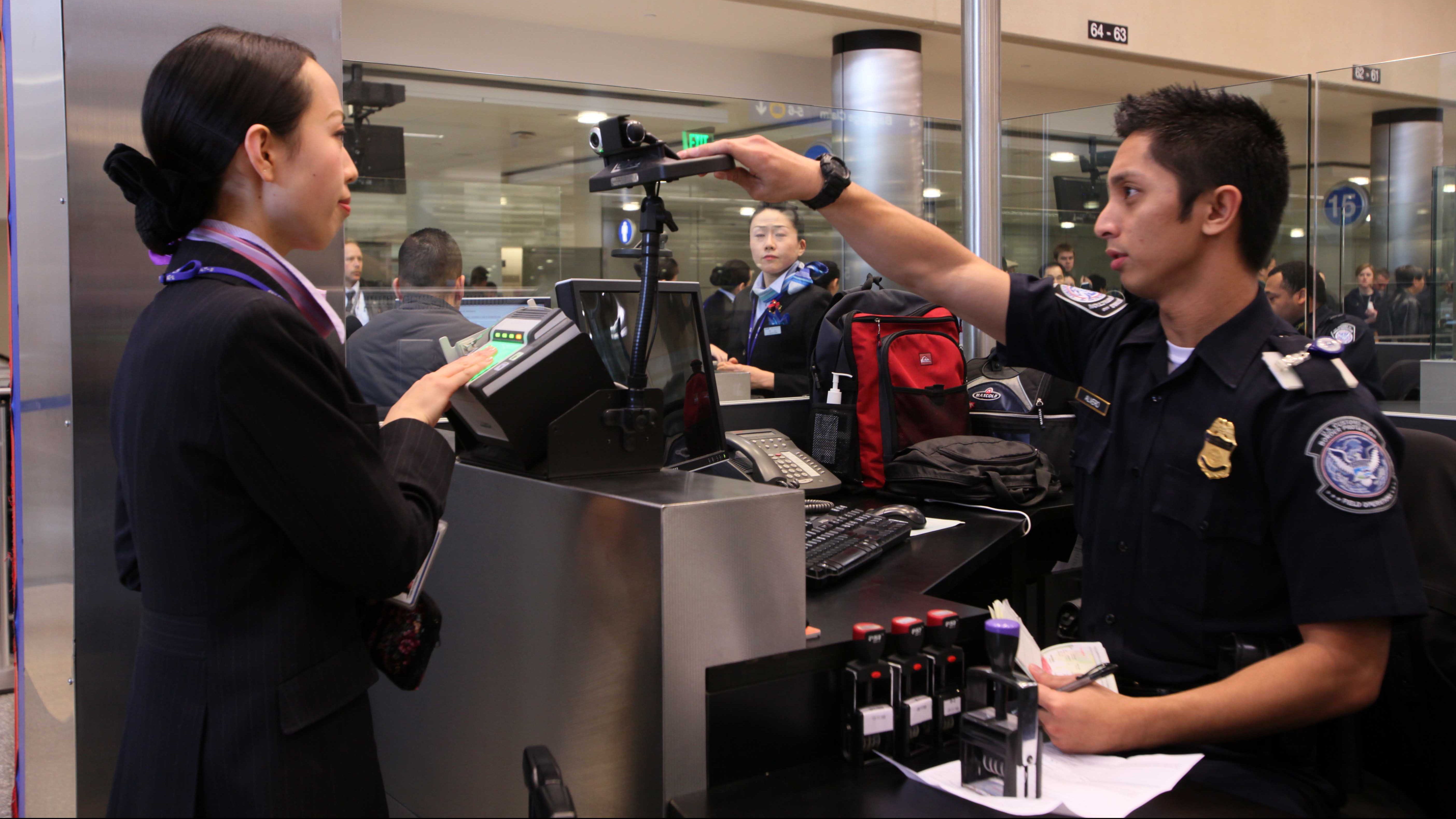 U.S Customs and Border Protection Officer Alveno Berenill takes photos of travelers as they arrive at Los Angeles International Airport on Thursday, Dec 10, 2009.