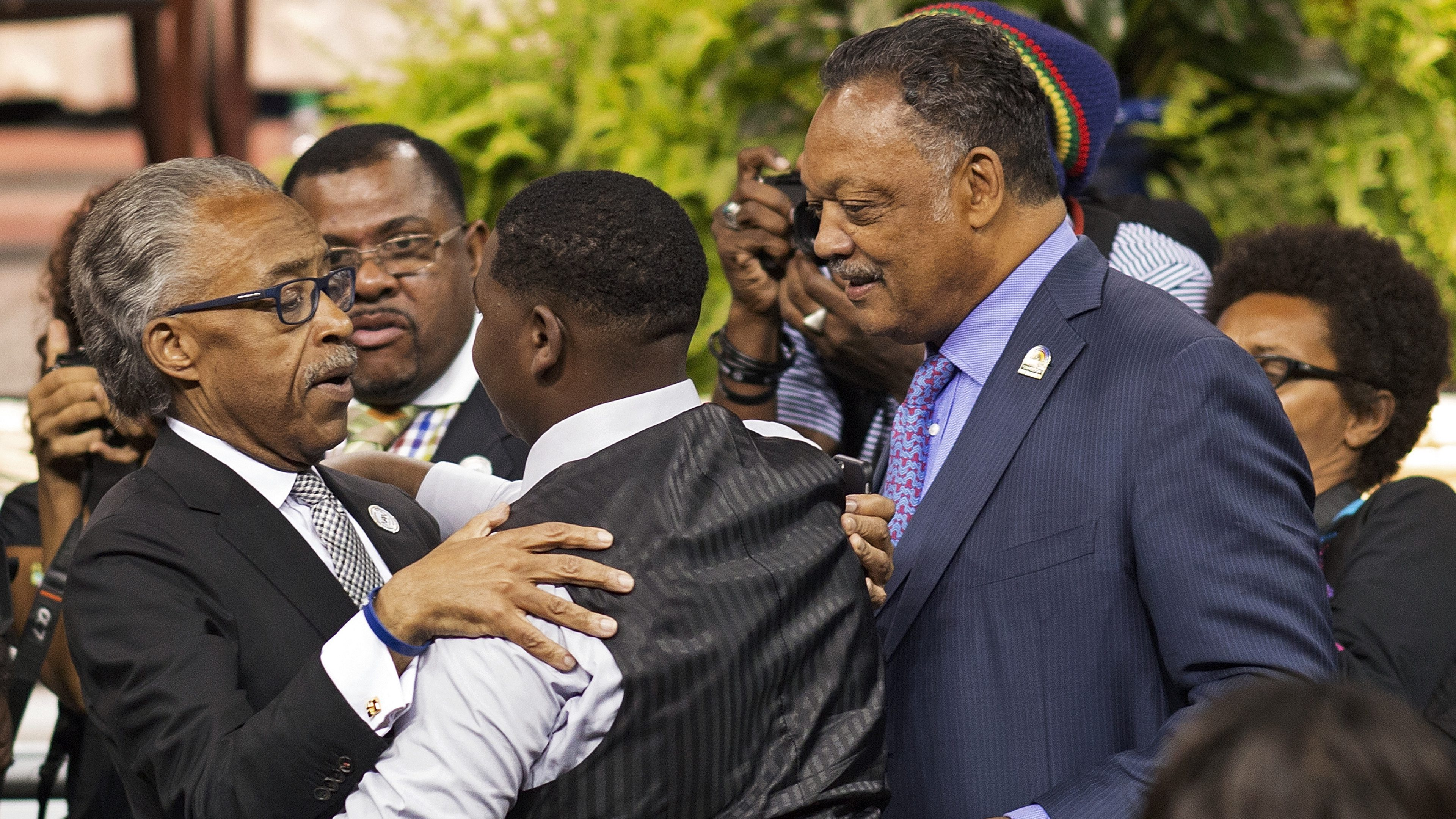 Civil rights leaders Rev. Al Sharpton, left, and Rev. Jesse Jackson, right, comfort Cameron Sterling, the son of Alton Sterling, during his father's funeral service at the F.G. Clark Activity Center in Baton Rouge, La., Friday, July 15, 2016. Alton Sterling was shot July 5 outside a Baton Rouge convenience store in an encounter with police that was caught on video.  (AP Photo/Max Becherer)