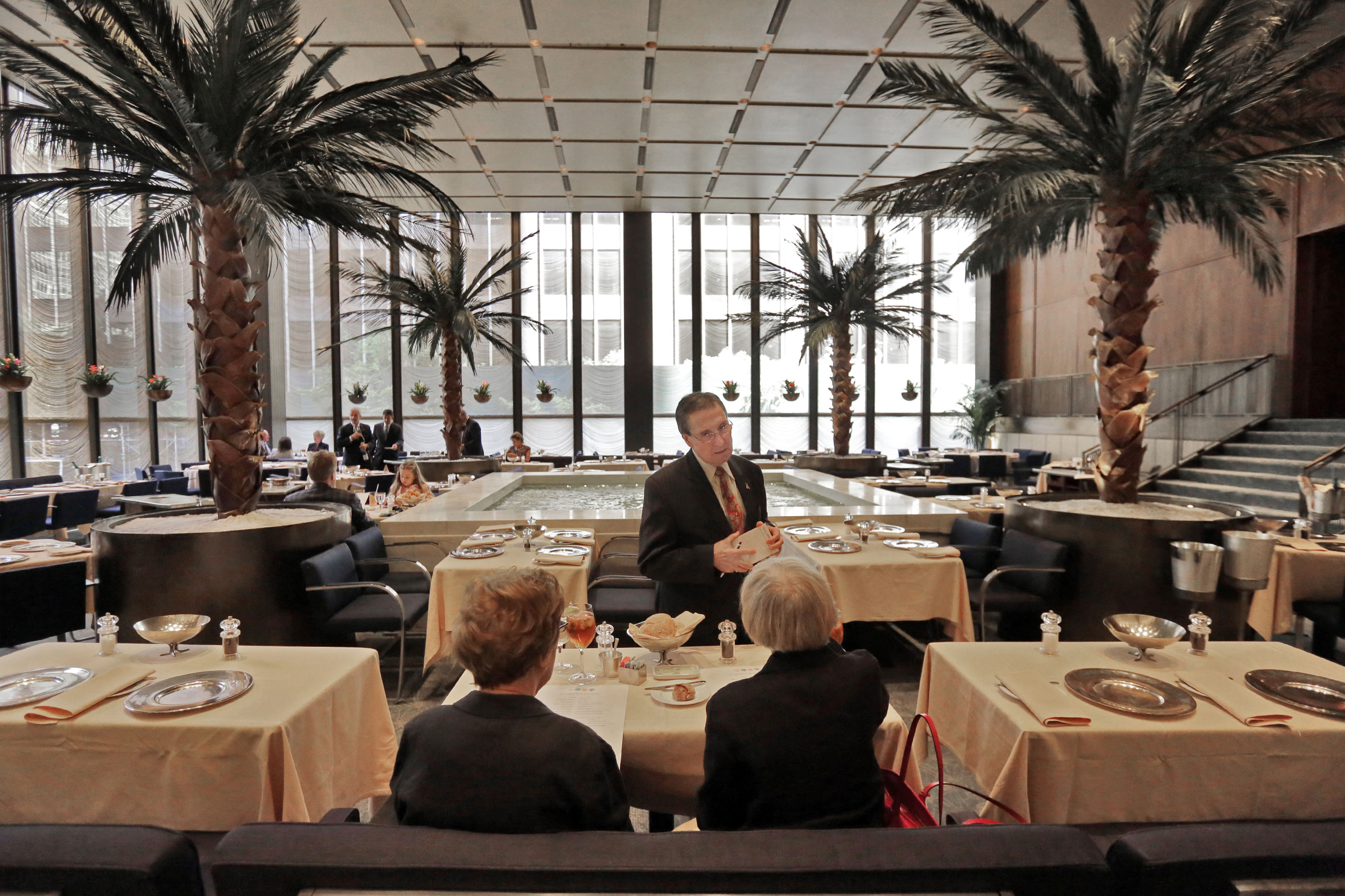In this July 12, 2016 photo, a waiter speaks with diners in the Pool Room of The Four Seasons, in New York's landmarked Seagram building, which has housed the restaurant for 57 years. Designed by the legendary architect Philip Johnson and the building's architect Ludwig Mies van der Rohe, the restaurant was a favorite of celebrities and business titans ever since it opened in 1959. The epitome of the midcentury style in Midtown Manhattan, The Four Seasons is scheduled to close on Saturday, July 16. (AP Photo/Richard Drew)