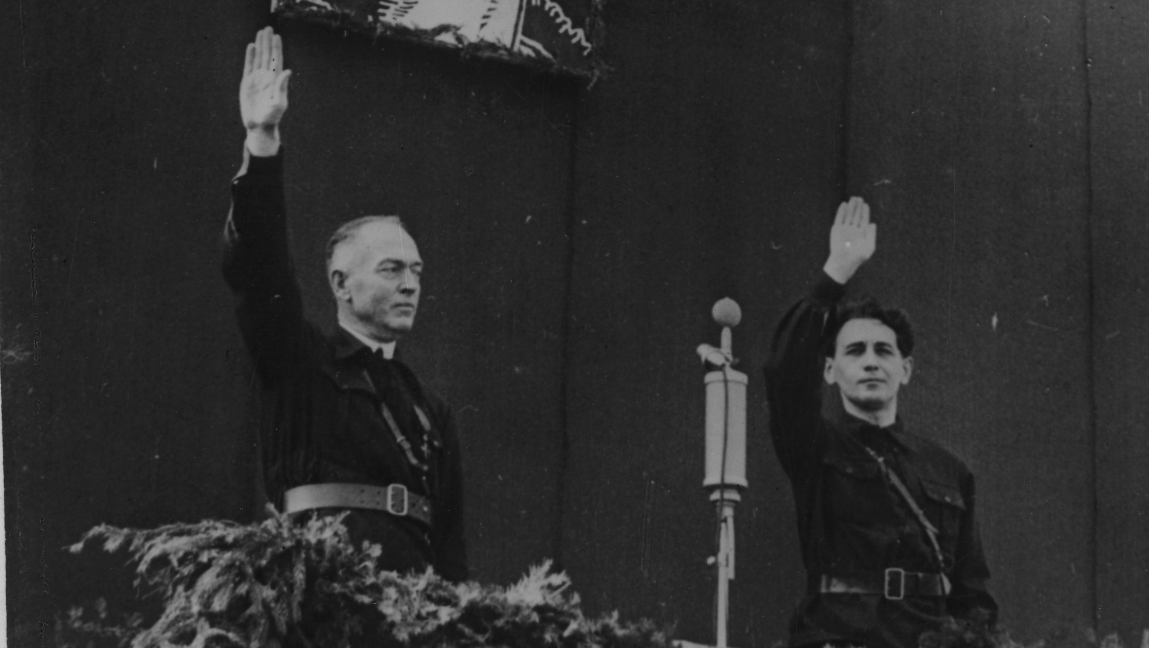 Leader of Romania's Legionnaire's Movement, Horia Sima, right, and Prime Minister Ion Antonescu, greet the crowd at a rally in Bucharest, Romania, October 10, 1940. Picture hanging above the two politicians portraits murdered legionnaire Corneliu Zelea Codreanu. (AP Photo)