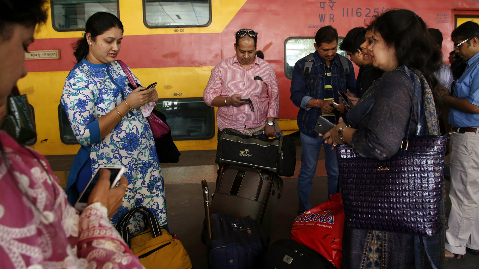 Indian travellers use a free WiFi service to browse the net at Mumbai Central Train Station in Mumbai, India, Friday, Jan. 22, 2016. Google Inc. has begun offering free WiFi to Mumbai train passengers in hopes of boosting its role in the Indian market, the first of 400 stations the company plans to eventually reach with the service.