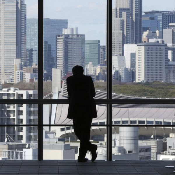 A man is silhouetted while watching toward high rise buildings at Shinjuku shopping and entertainment district in in Tokyo, Friday, March 25, 2016.