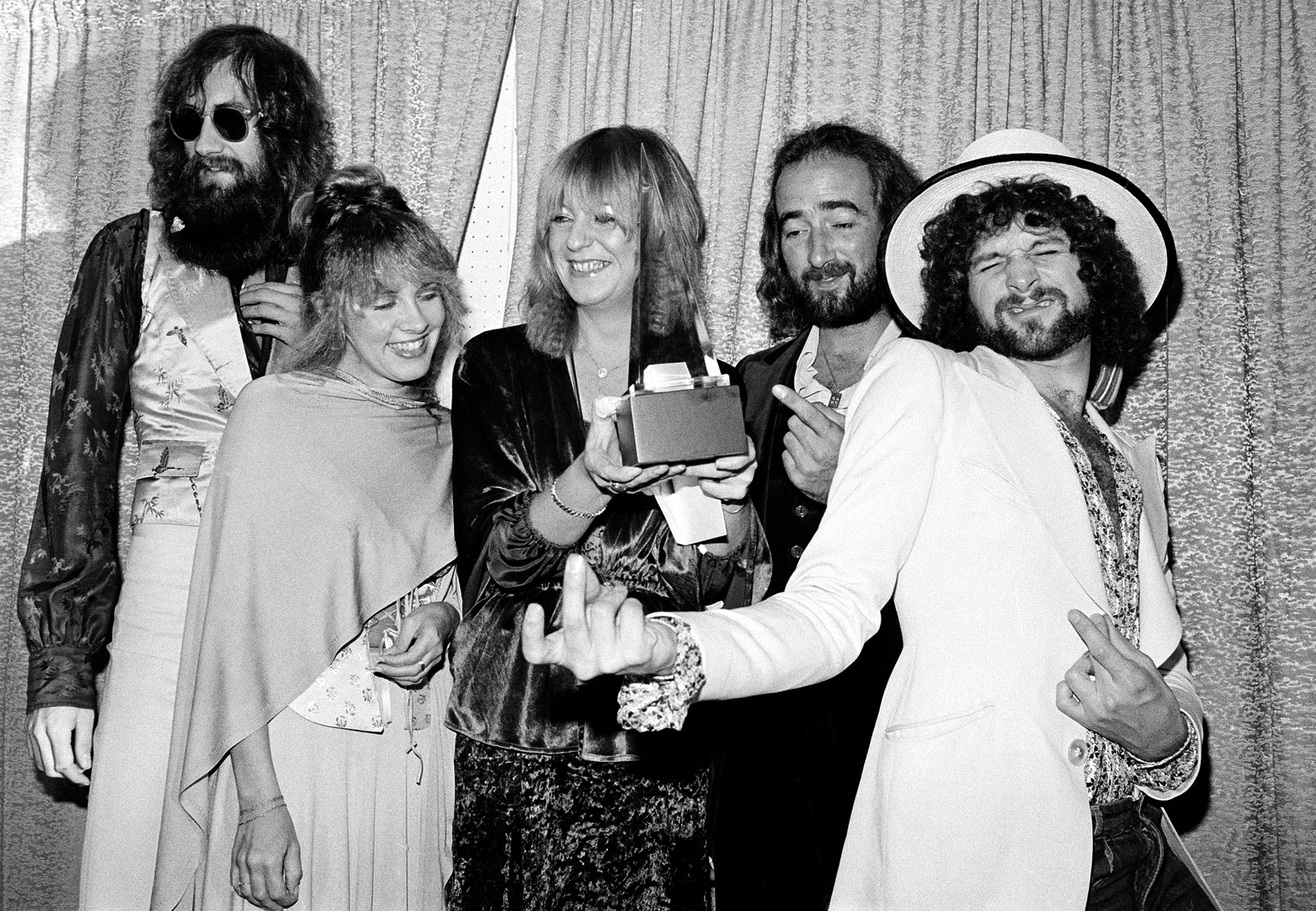 "Members of the singing group Fleetwood Mac pose with their award at the American Music Awards show in Santa Monica, Ca., Jan. 16, 1978. The group was named favorite pop group and ""Rumours"" was named favorite album in the pop category. Posing from left are, Mick Fleetwood, wearing sunglasses; Stevie Nicks; Christine McVie; John McVie; and Lindsey Buckingham. (AP Photo/Nick Ut)"