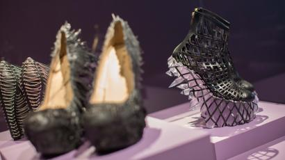 "3D-printed shoes created by designer Iris van Herpen sit on display at the High Museum's new exhibit, ""Iris van Herpen: Transforming Fashion"", Thursday, Nov. 5, 2015, in Atlanta. The exhibit, running through May 15, shows the evolution of van Herpen's design from collections created from 2008 through 2015. Van Herpen is known for creating high-tech fabrics and fashions that combine materials like steel and silk with everyday objects like magnets and umbrella parts. (AP Photo/Branden Camp)"