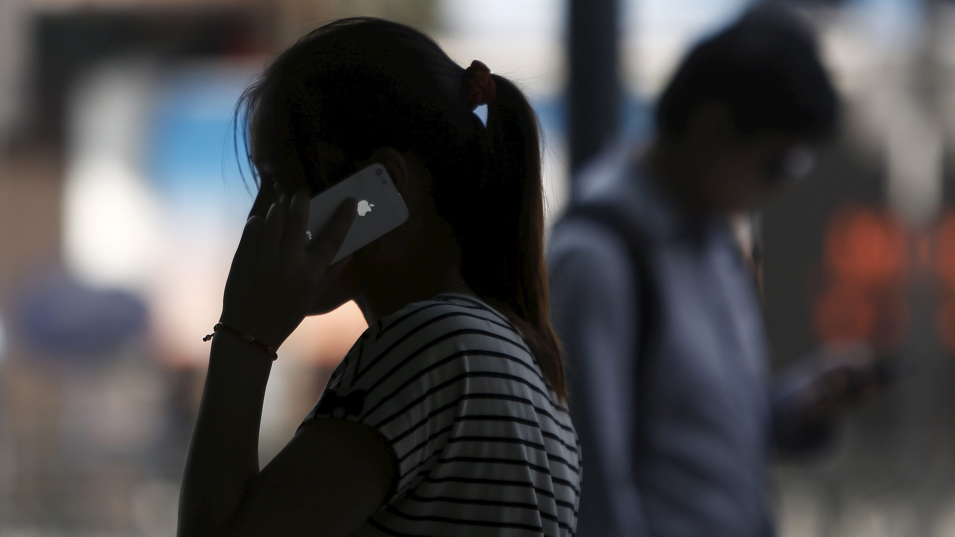 A woman speaks on her iPhone as she walks on a busy street in downtown Shanghai September 10, 2013. REUTERS/Aly Song/File Photo - RTX2BV9H