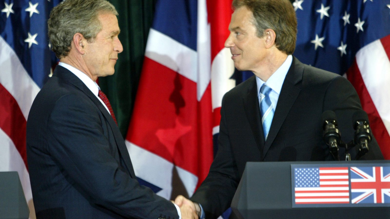 President George W. Bush and British Prime Minister Tony Blair shake hands after a joint press conference following their meeting at Hillsborough Castle near Belfast April 8, 2003. Picture taken April 8, 2003. REUTERS/Kevin Lamarque/File Photo - RTX2JUNZ