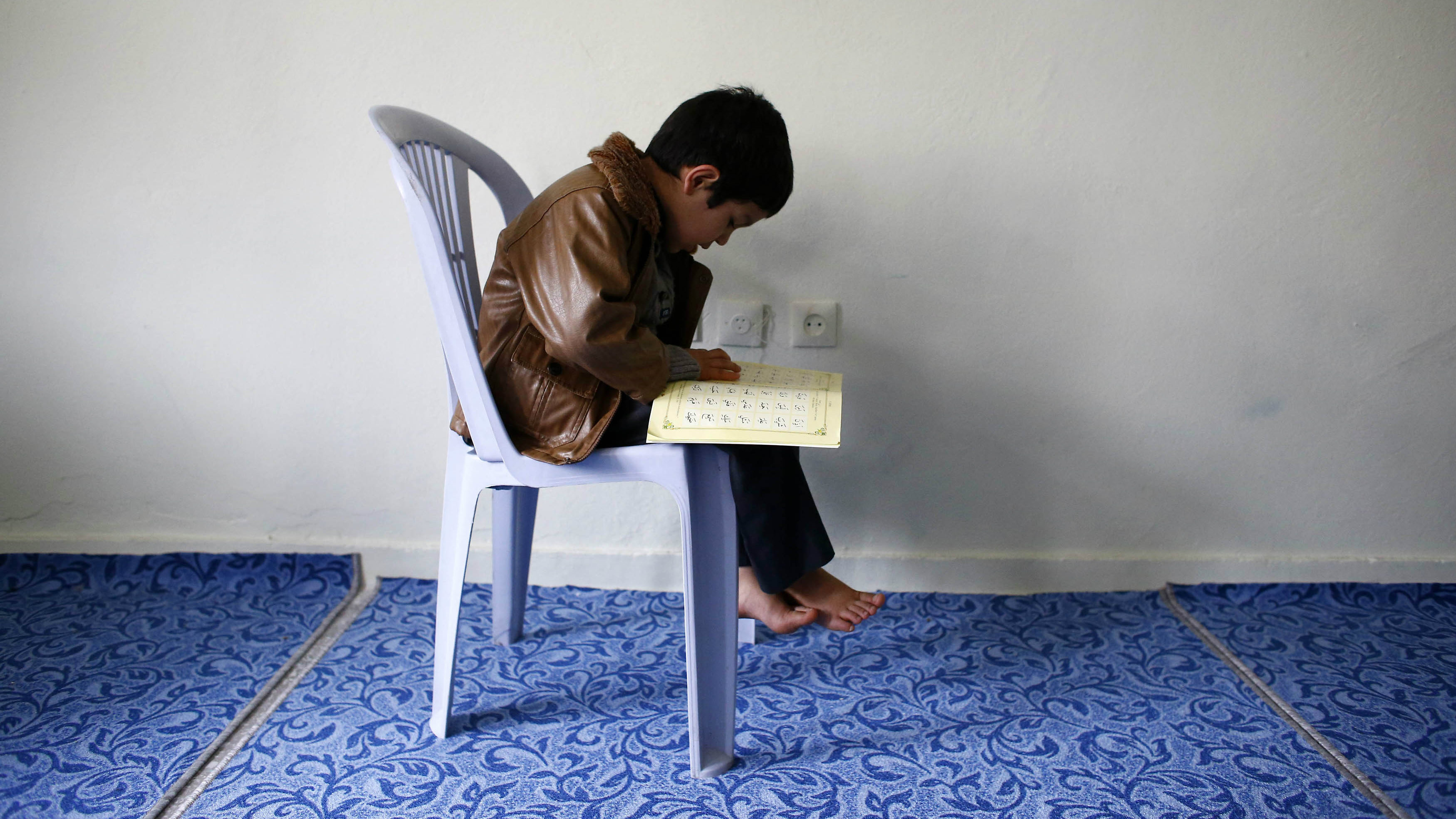 An Uighur refugee boy reads the Koran where he is housed in a gated complex in the central city of Kayseri, Turkey, February 11, 2015. Thousands of members of China's Turkic language-speaking Muslim ethnic minority have reached Turkey, mostly since last year, infuriating Beijing, which accuses Ankara of helping its citizens flee unlawfully. Turkish officials deny playing any direct role in assisting the flight. Picture taken February 11, 2015. To match Insight TURKEY-CHINA/UIGHURS REUTERS/Umit Bektas
