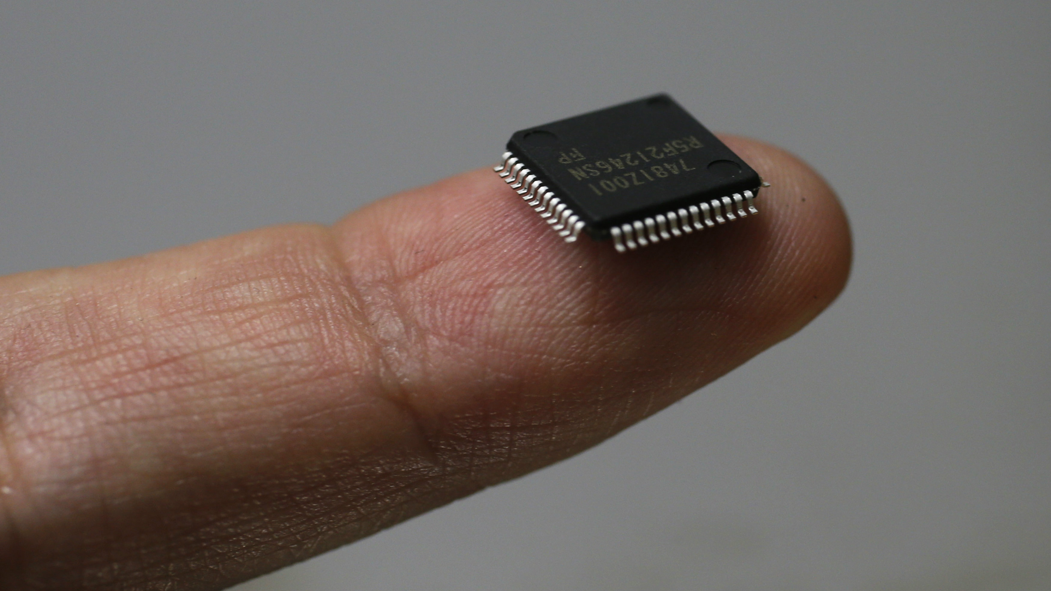 A Renesas Electronics Corp's microcontroller chip sits on a finger in this illustrative photograph taken in Tokyo May 24, 2012. Japan's loss-making Renesas Electronics Corp said on Thursday it will tie up with Taiwan Semiconductor Manufacturing Co in the microchip business as it struggles to keep up with aggressive rivals like Samsung Electronics. REUTERS/Kim Kyung-Hoon (JAPAN - Tags: BUSINESS SCIENCE TECHNOLOGY)