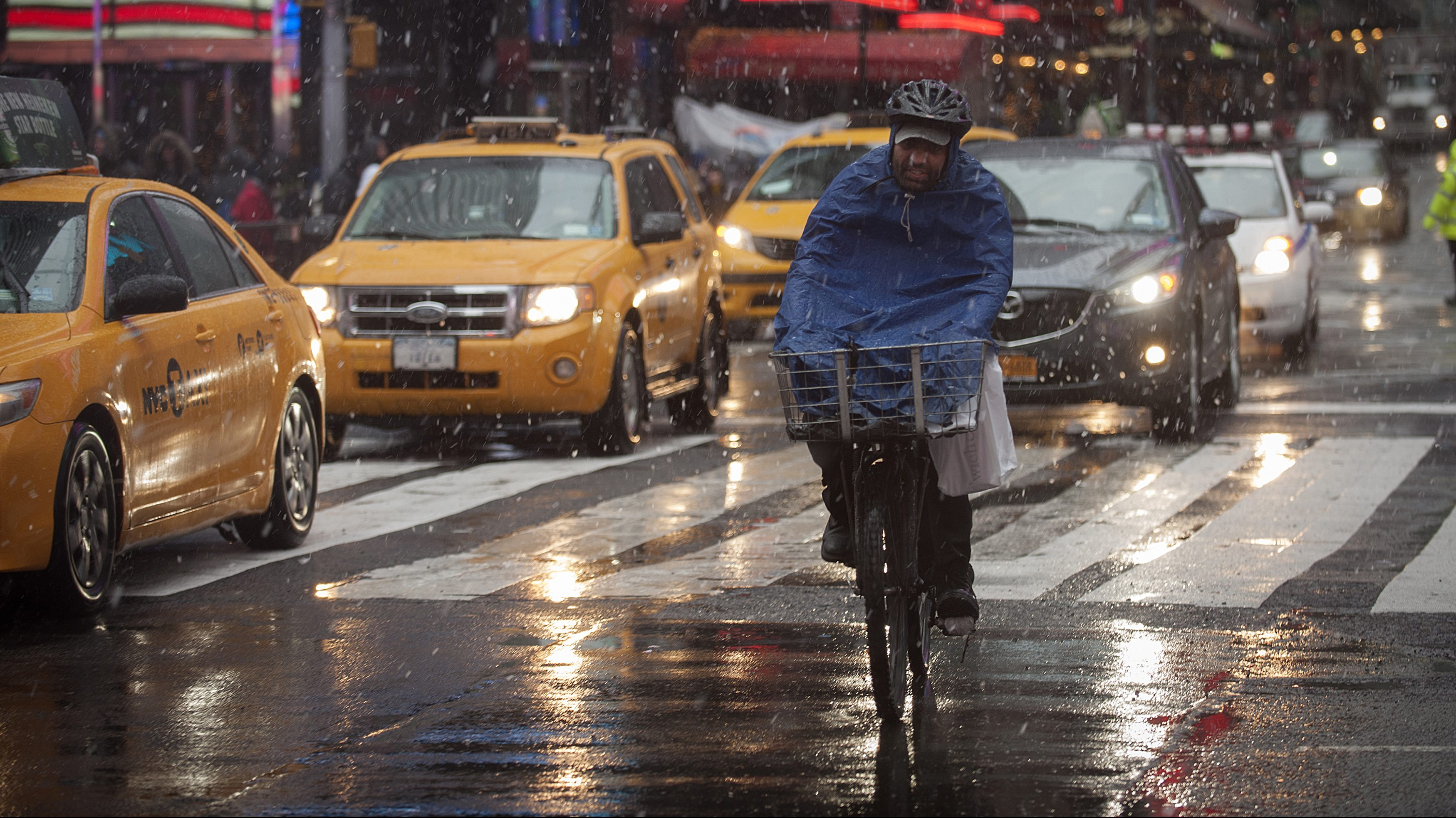 A bike delivery man makes his way through the snow in New York's Times Square December 29, 2012. REUTERS/Keith Bedford (UNITED STATES - Tags: ENVIRONMENT SOCIETY) - RTR3BYYH