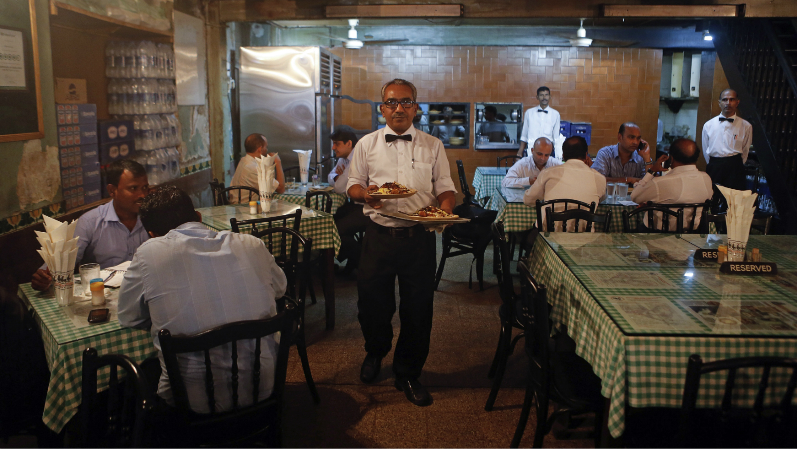 A waiter carries plates of food for customers at the Britannia and Co. restaurant in Mumbai September 19, 2013. The aroma of frying onions from the Britannia and Co. restaurant might not penetrate the office of Reserve Bank of India (RBI) Governor Raghuram Rajan a block away, but like the eatery's customers, he can't escape the soaring price of the pungent vegetable.