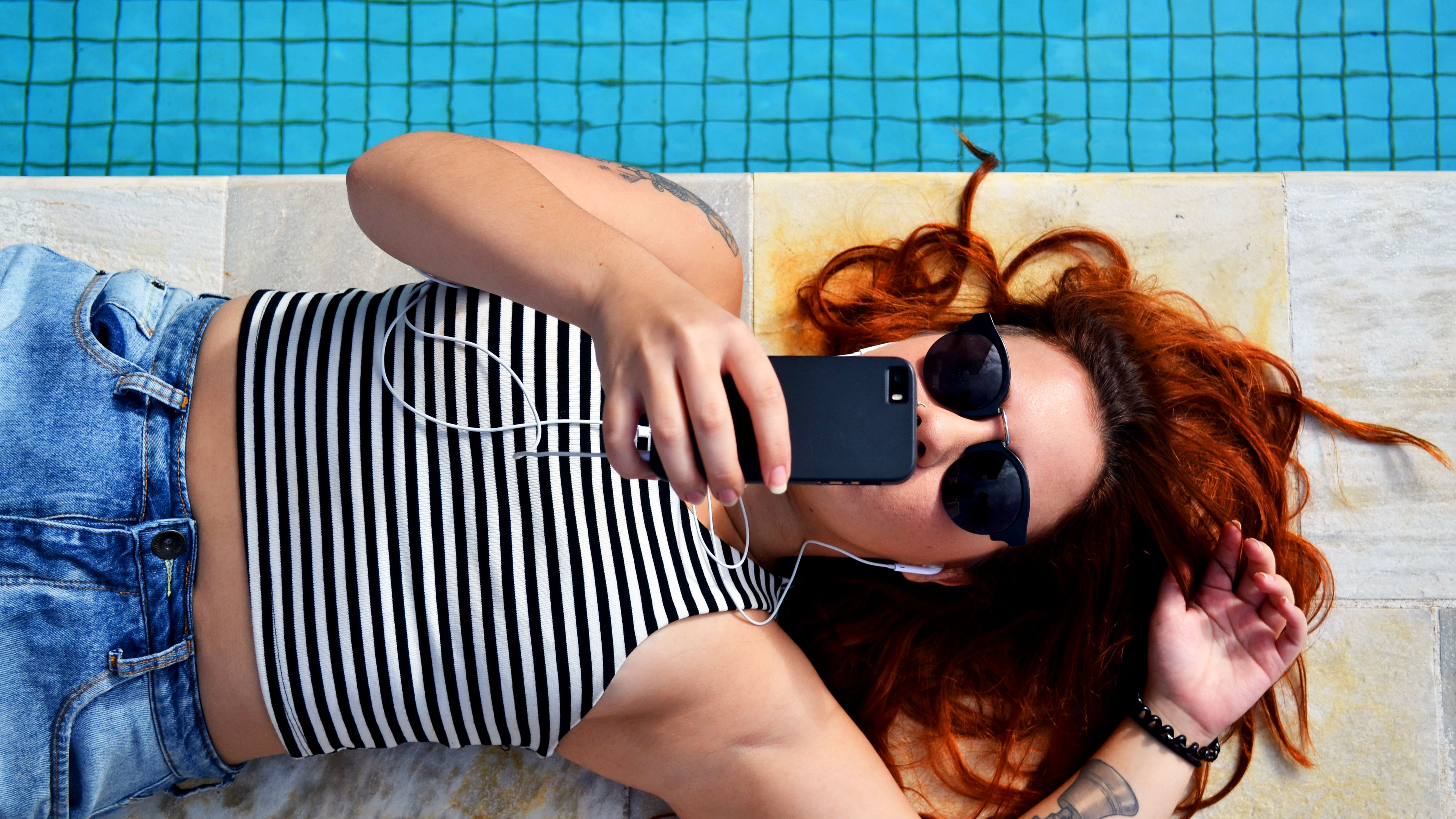 girl laying on her back and holding a cell phone next to a pool
