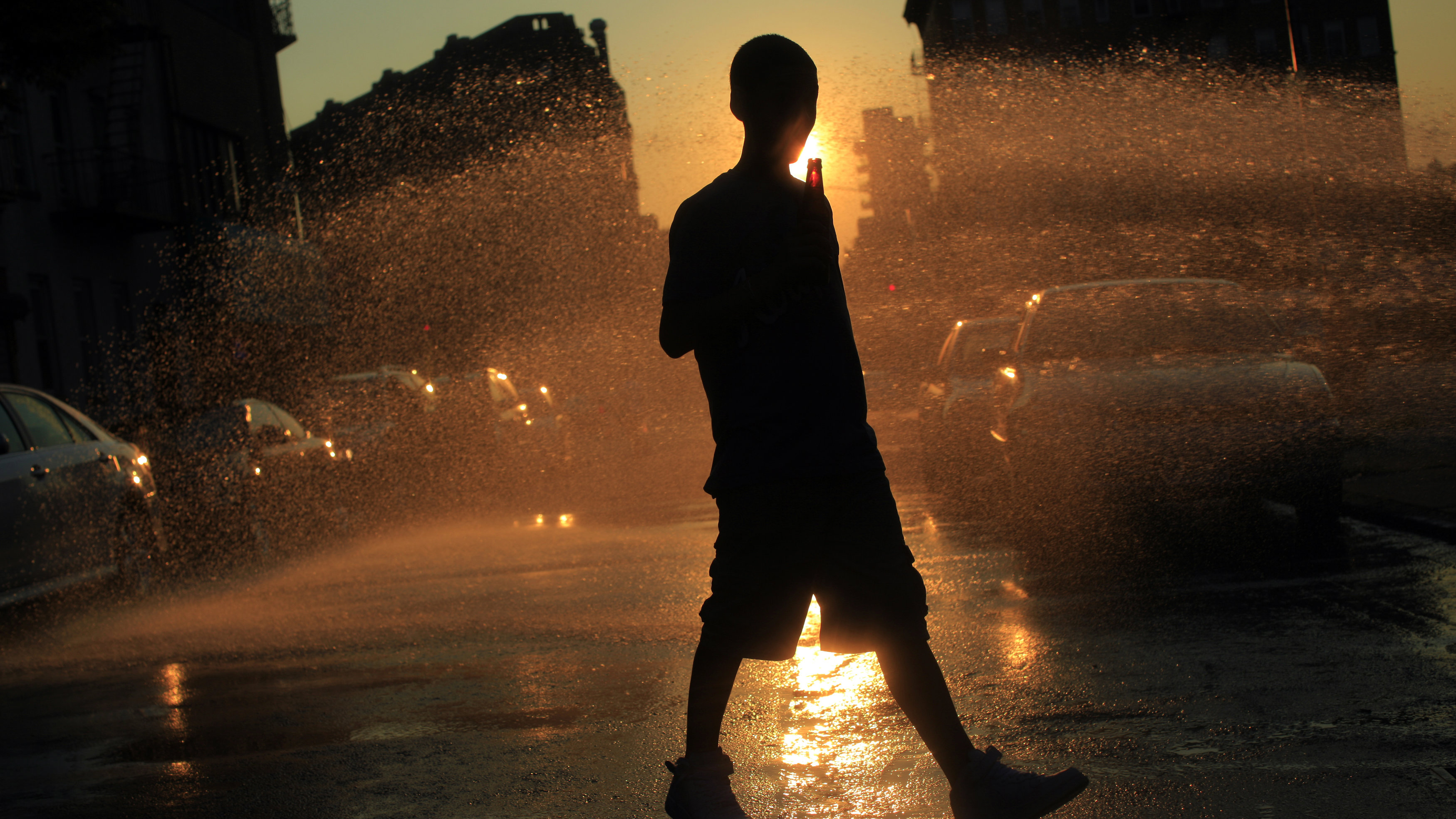 A boy walks near water spraying from an open fire hydrant in the Williamsburg neighborhood of Brooklyn, New York July 5, 2010. Temperatures soared toward 100 degrees or more Tuesday along much of the East Coast after an extended Fourth of July weekend when temperatures inched into at least the 90s from Maine to Texas. REUTERS/Eric Thayer