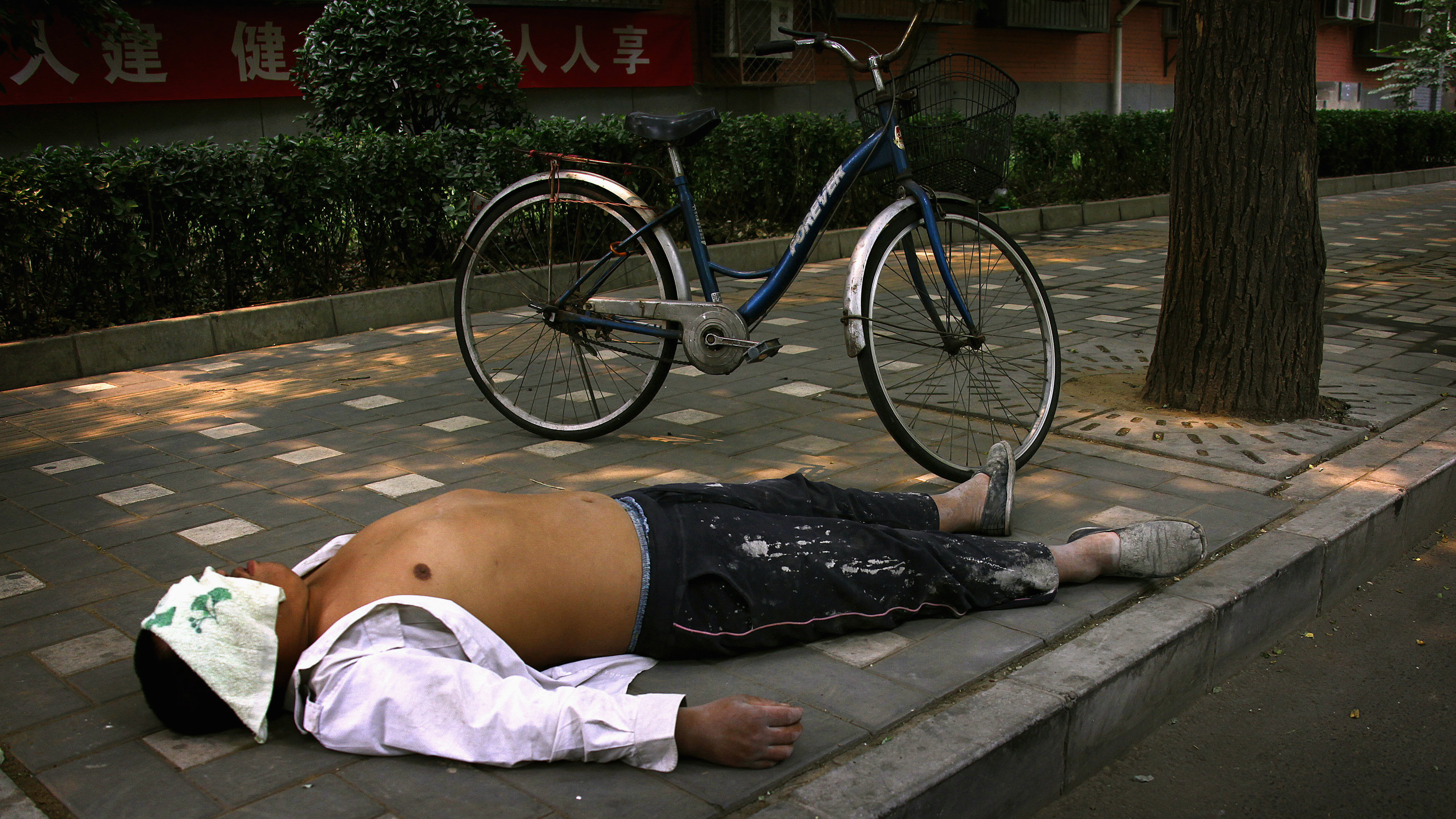 """A man sleeps next to his bicycle on a footpath along a Chinese alley known as a """"Hutong'', during a hot day in central Beijing June 21, 2012. REUTERS/David Gray"""