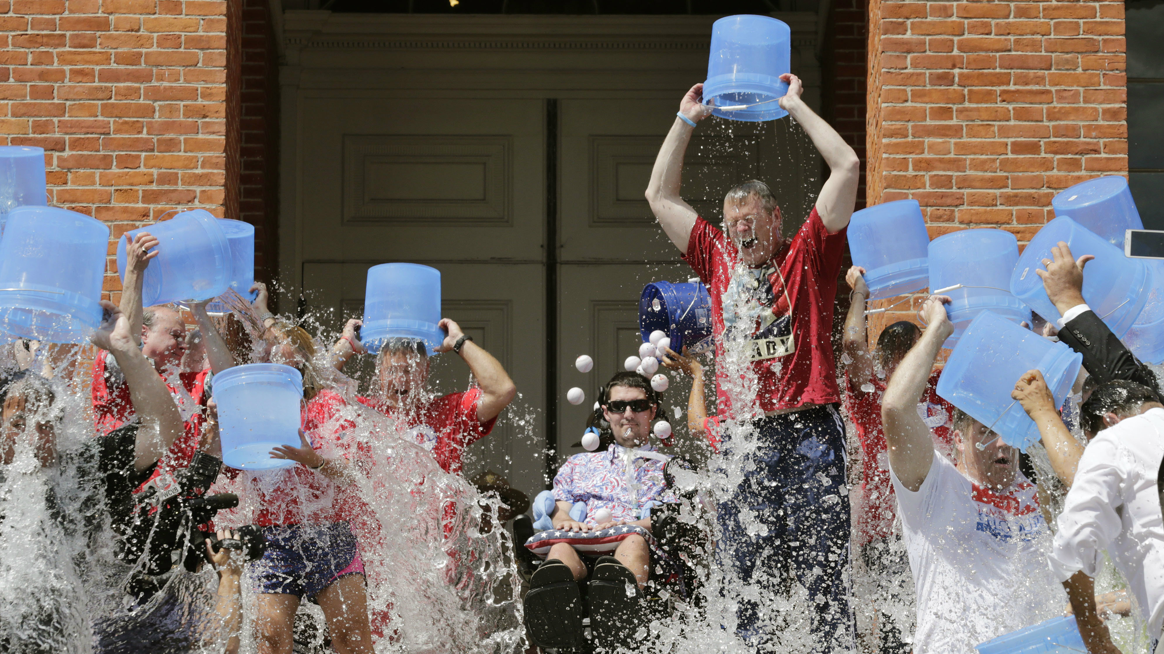 Massachusetts Gov. Charlie Baker, right center, and Lt. Gov. Karyn Polito, third from left, participate in the Ice Bucket Challenge with its inspiration Pete Frates, seated in center, to raise money for ALS research, Monday, Aug. 10, 2015, at the Statehouse in Boston. (AP Photo/Charles Krupa)