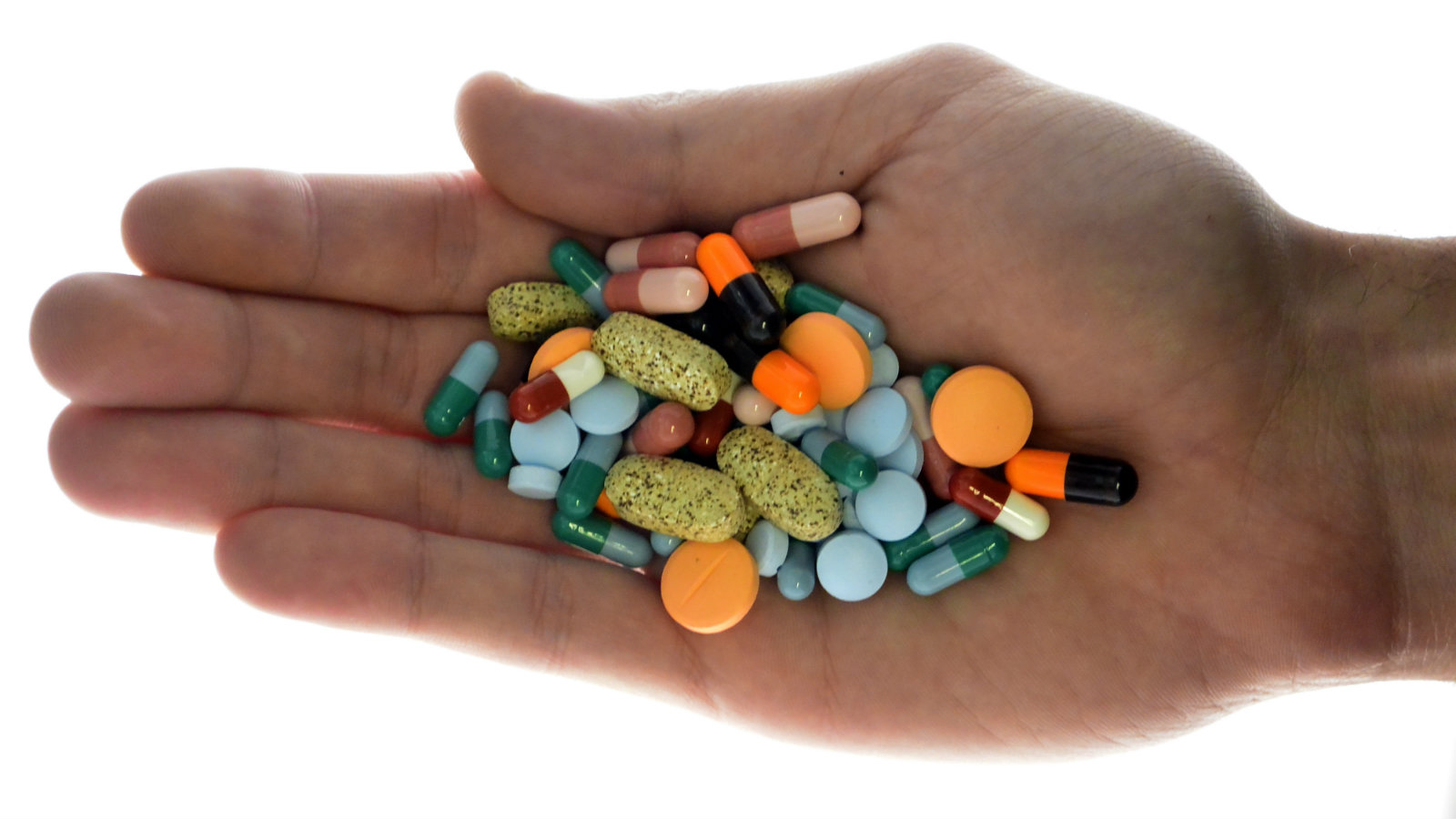A person holds pharmaceutical tablets and capsules in this picture illustration taken in Ljubljana September 18, 2013. Picture taken September 18.