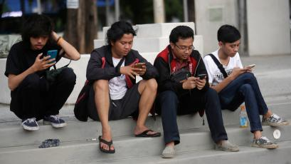 "In this Monday, July 18, 2016 photo, people gaze at their smartphones as they play ""Pokemon Go"" in Jakarta, Indonesia. Indonesian authorities banned the playing of ""Pokemon Go"" from the presidential palace on Wednesday, July 20, 2016, as they voiced worries that the game could be a security risk. (AP Photo/Tatan Syuflana)"