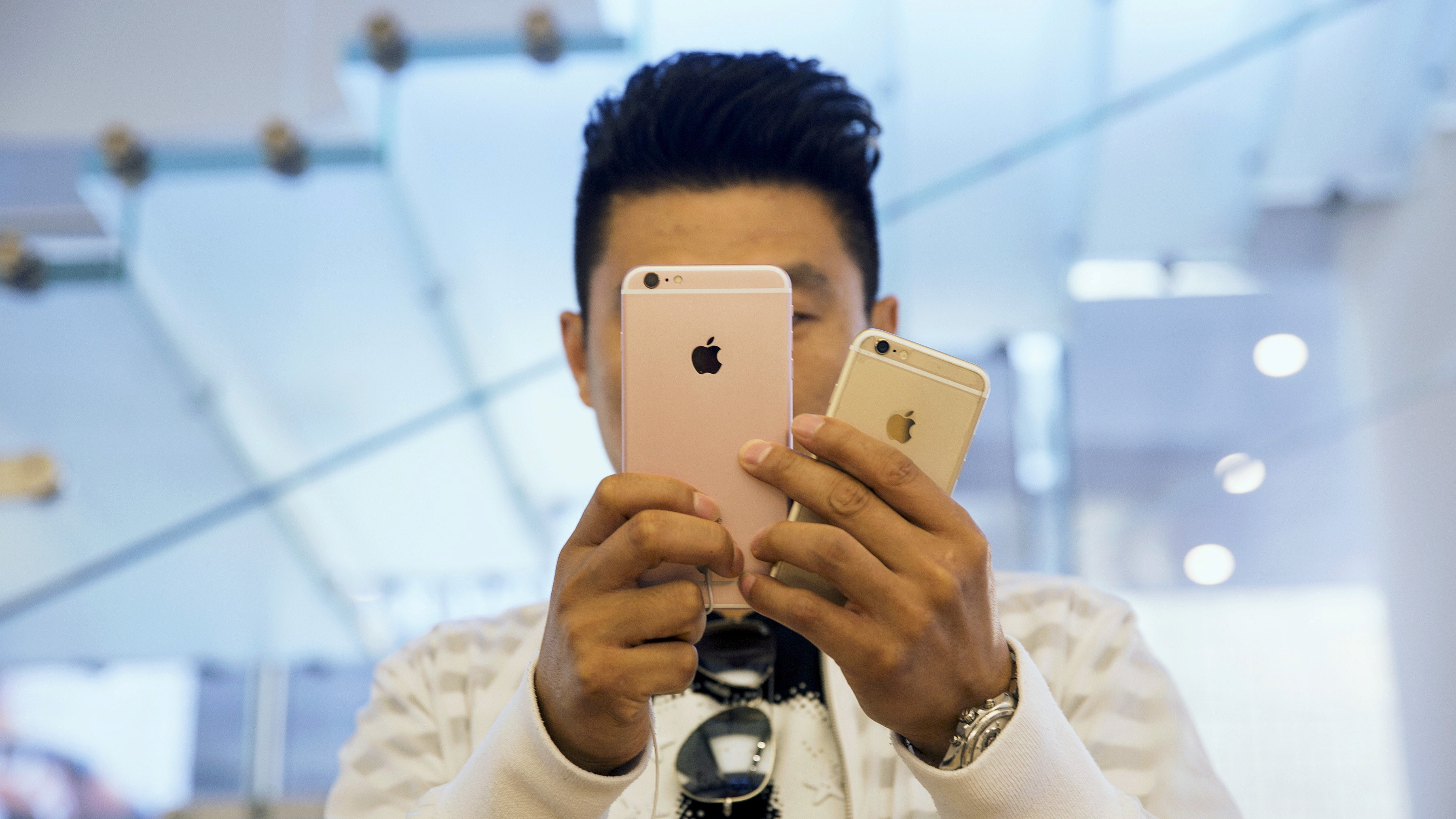 A man takes pictures as Apple iPhone 6s and 6s Plus go on sale at an Apple Store in Beijing, China September 25, 2015. REUTERS/Damir Sagolj/File Photo - RTSJD26