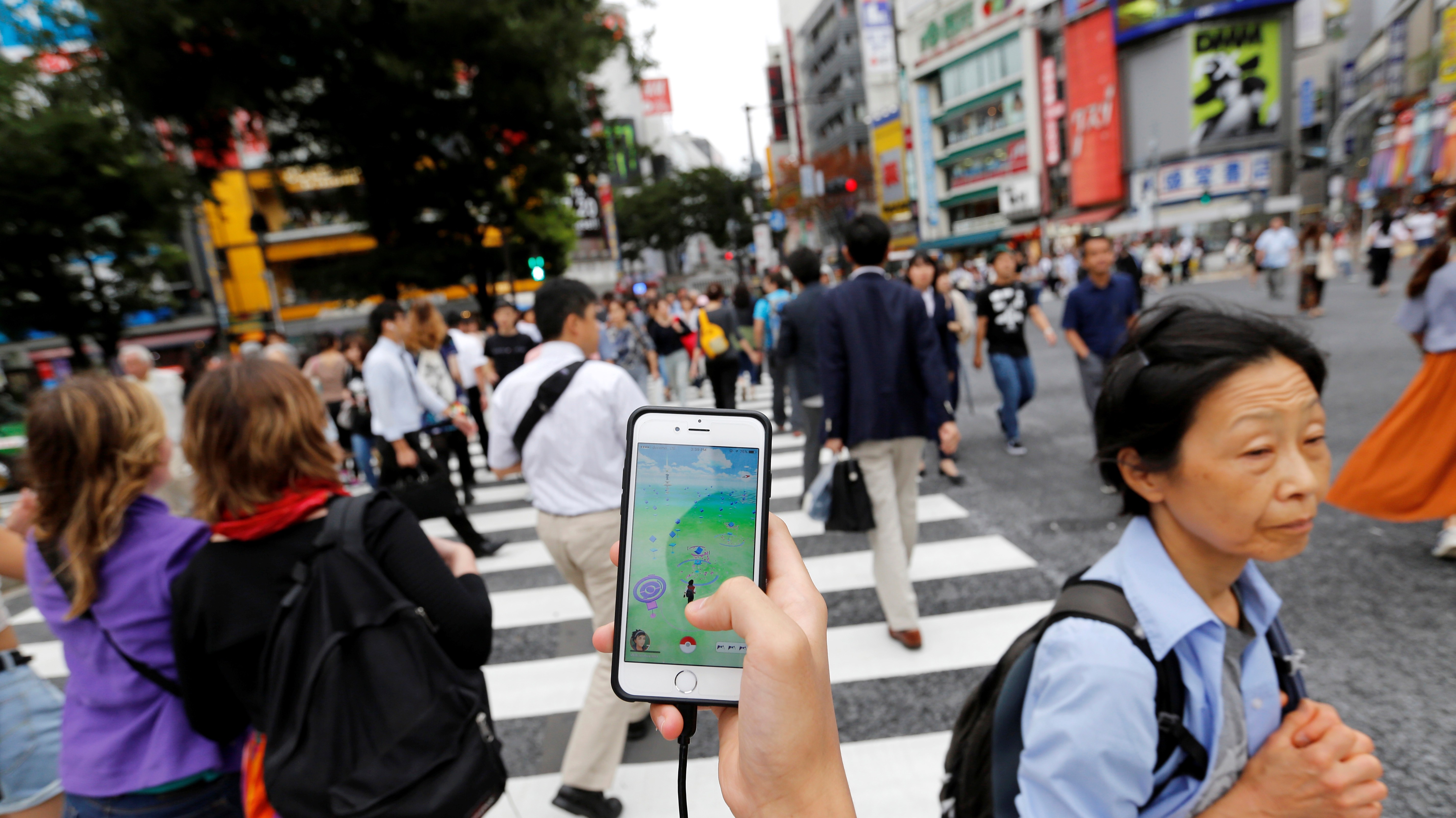 """A man plays the augmented reality mobile game """"Pokemon Go"""" by Nintendo on his mobile phone as he walks at a busy crossing in Shibuya district in Tokyo, Japan, July 22, 2016. REUTERS/Toru Hanai - RTSJ5OU"""