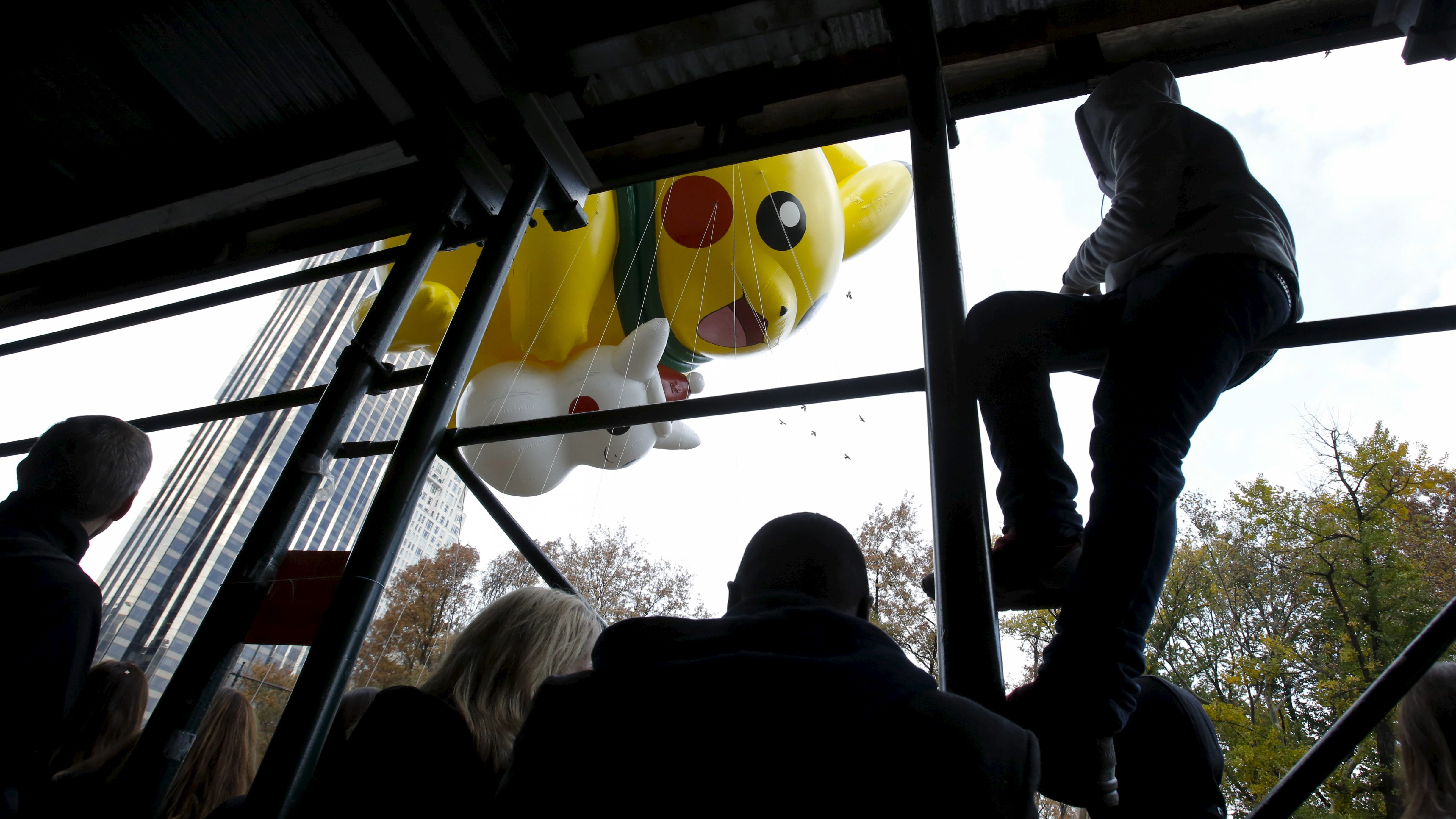 "People watch through scaffolding as the ""Pikachu"" balloon from Pokemon floats down Central Park South during the 89th Macy's Thanksgiving Day Parade in the Manhattan borough of New York, November 26, 2015."